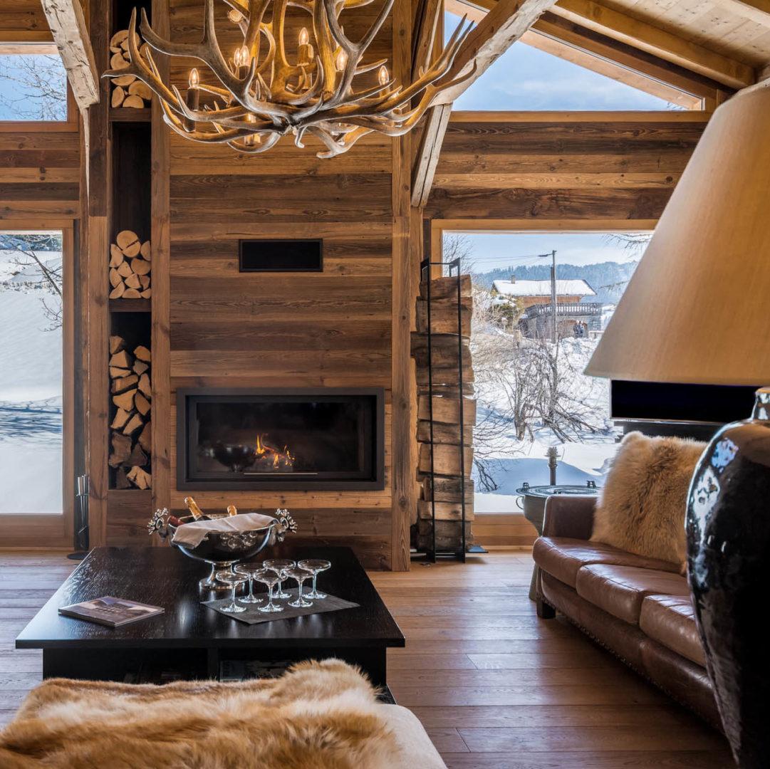 Chalet Ferme de la Corderie Les Gets Les Portes du Soleil Frankrijk wintersport skivakantie luxe living open haard kroonluchter bank Champagne glazen uitzicht sneeuw