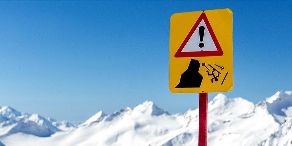Reisverzekering wintersport skivakantie luxe waarschuwingsbord sneeuw
