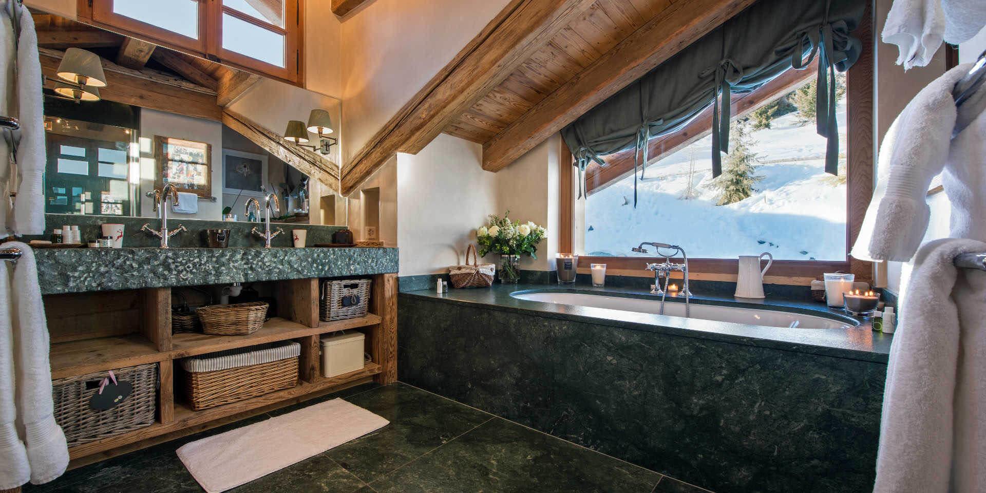 Chalet Nyumba Verbier Les 4 Vallees Zwitserland wintersport skivakantie luxe badkamer bad dubbele wasbak kastje handdoeken spiegel raam uitzicht sneeuw Bamford Organic Bath & Body-producten