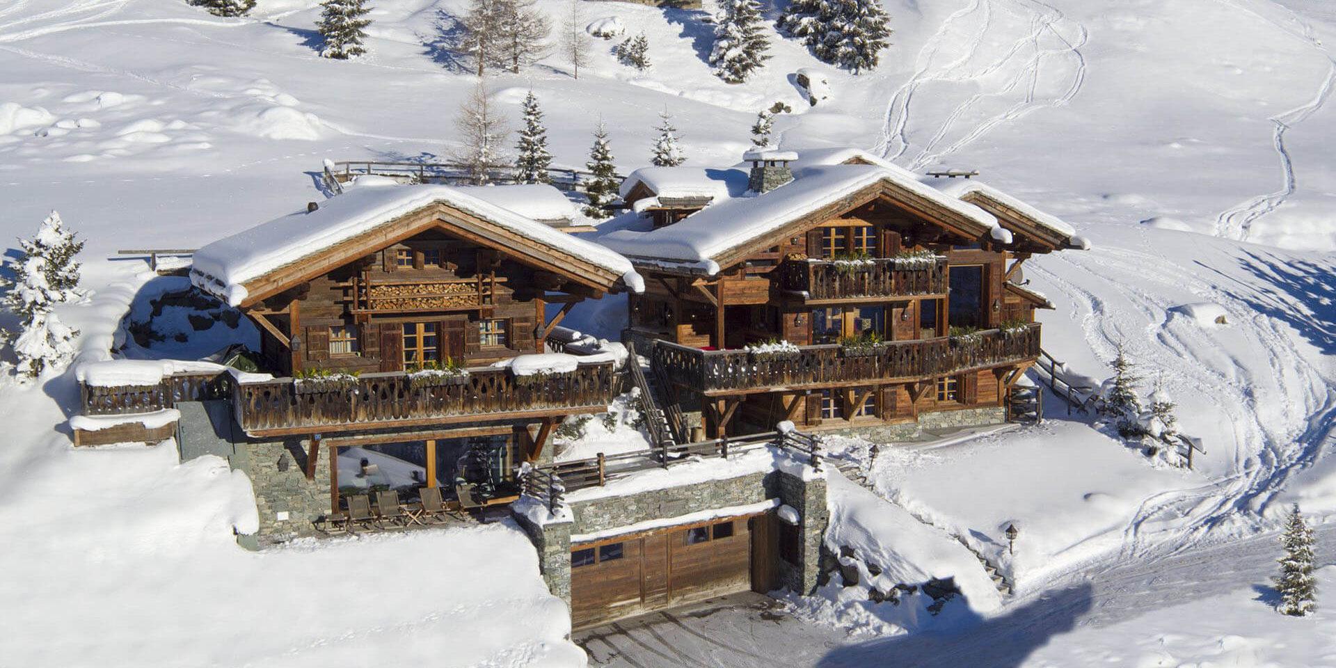 Chalet Nyumba Verbier Les 4 Vallees Zwitserland wintersport skivakantie luxe voorkant chalet garage terras ligstoelen sneeuw bomen