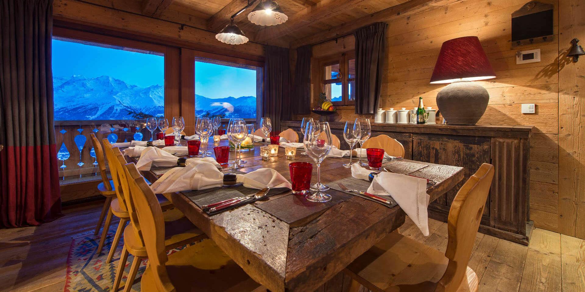 Chalet Nyumba Verbier Les 4 Vallees Zwitserland wintersport skivakantie luxe eetkamer gedekte tafel stoelen wijnglazen lamp balkon uitzicht bergen sneeuw