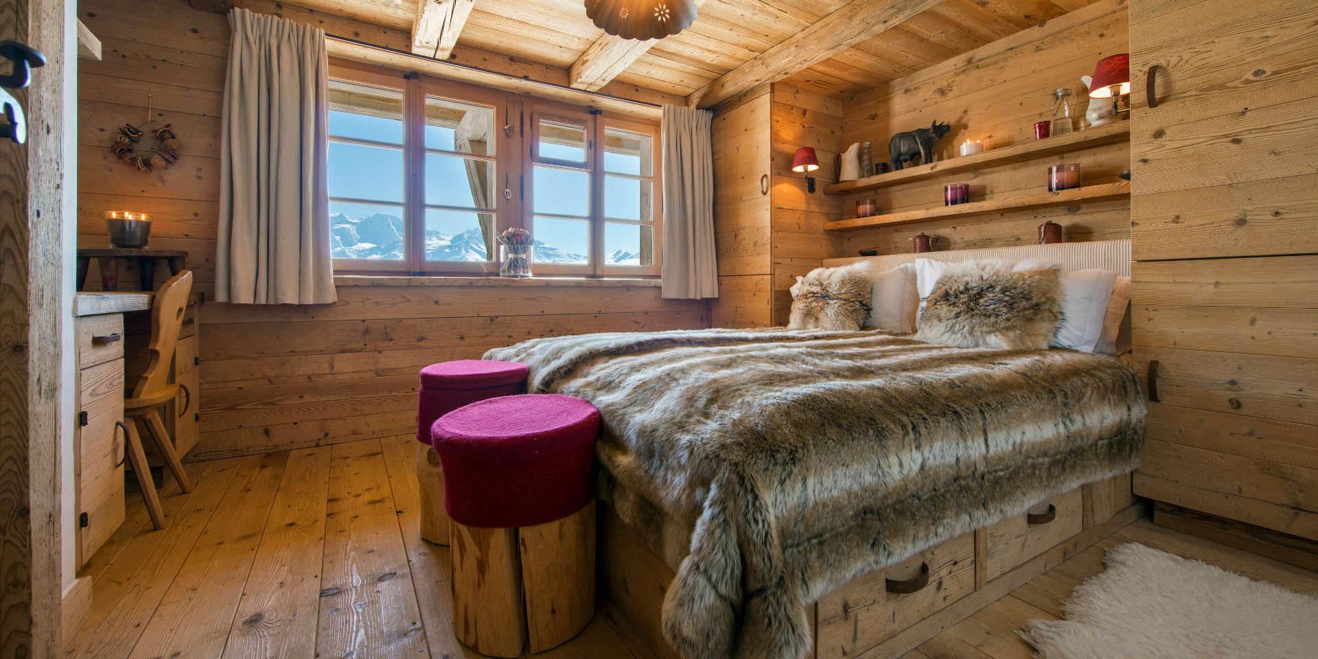 Chalet Nyumba Verbier Les 4 Vallees Zwitserland wintersport skivakantie luxe slaapkamer 2-persoonsbed hocker bureau stoel kaarsen decoratie raam