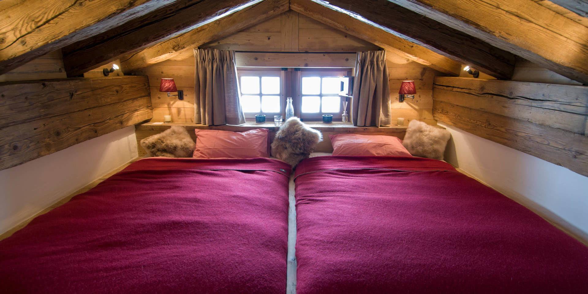 Chalet Nyumba Verbier Les 4 Vallees Zwitserland wintersport skivakantie luxe slaapkamer aparte bedden houten balken onder dak ramen knus