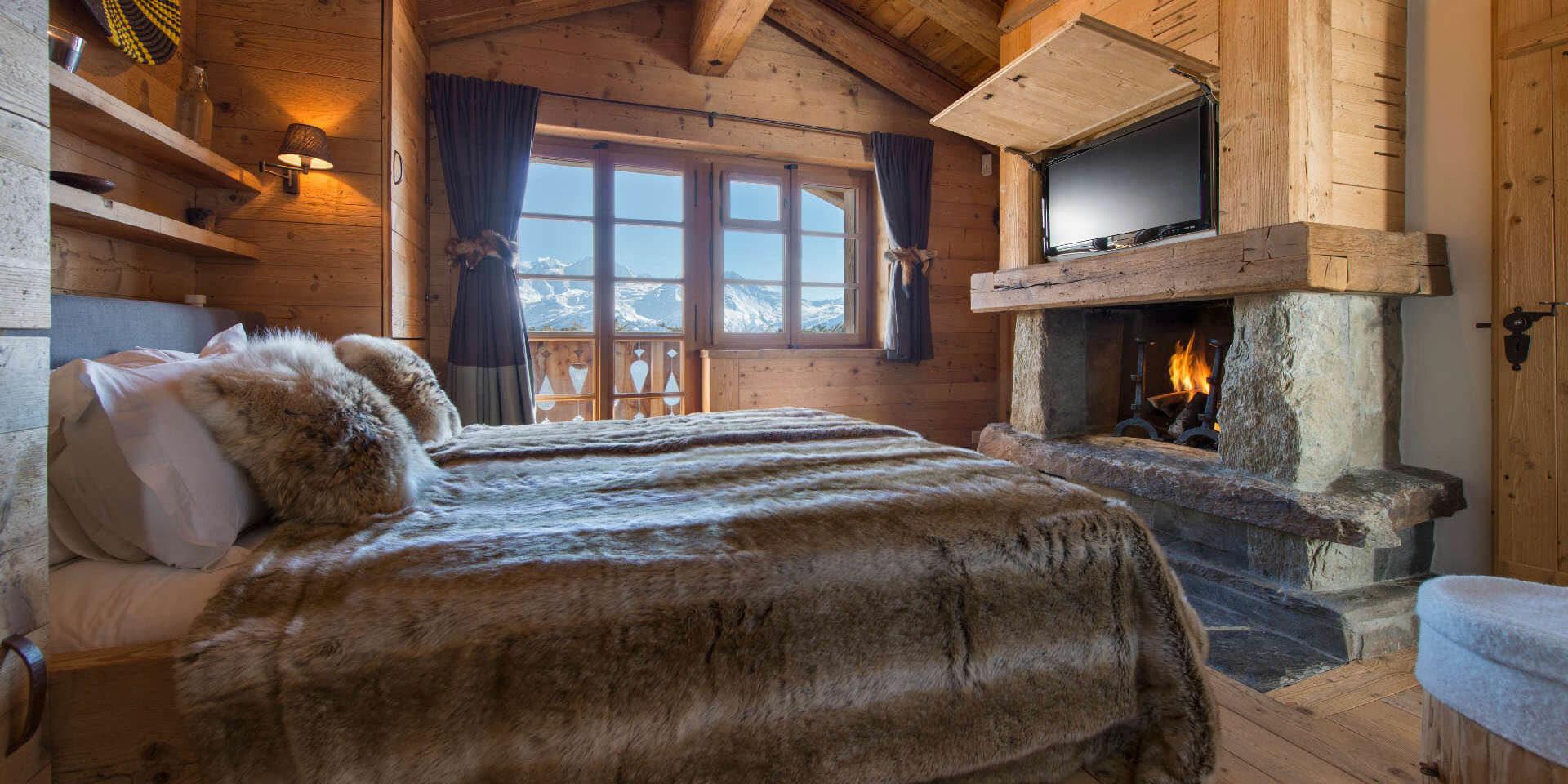 Chalet Nyumba Verbier Les 4 Vallees Zwitserland wintersport skivakantie luxe slaapkamer 2-persoonsbed open haard bedsprei hocker TV raam balkon