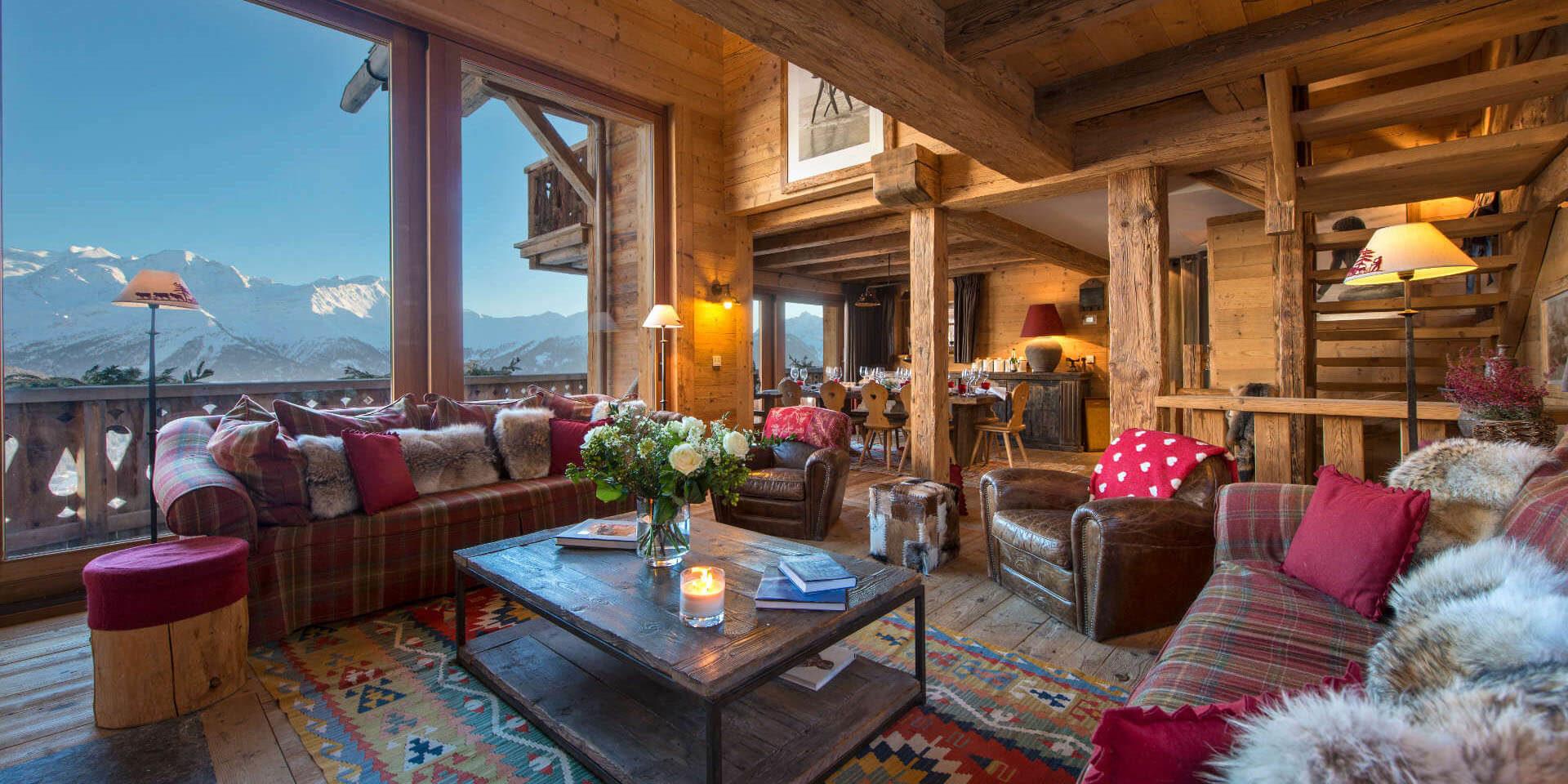 Chalet Nyumba Verbier Les 4 Vallees Zwitserland wintersport skivakantie luxe living banken kussens fauteuils hocker salontafel hout trap eetkamer groot raam uitzicht bergen sneeuw