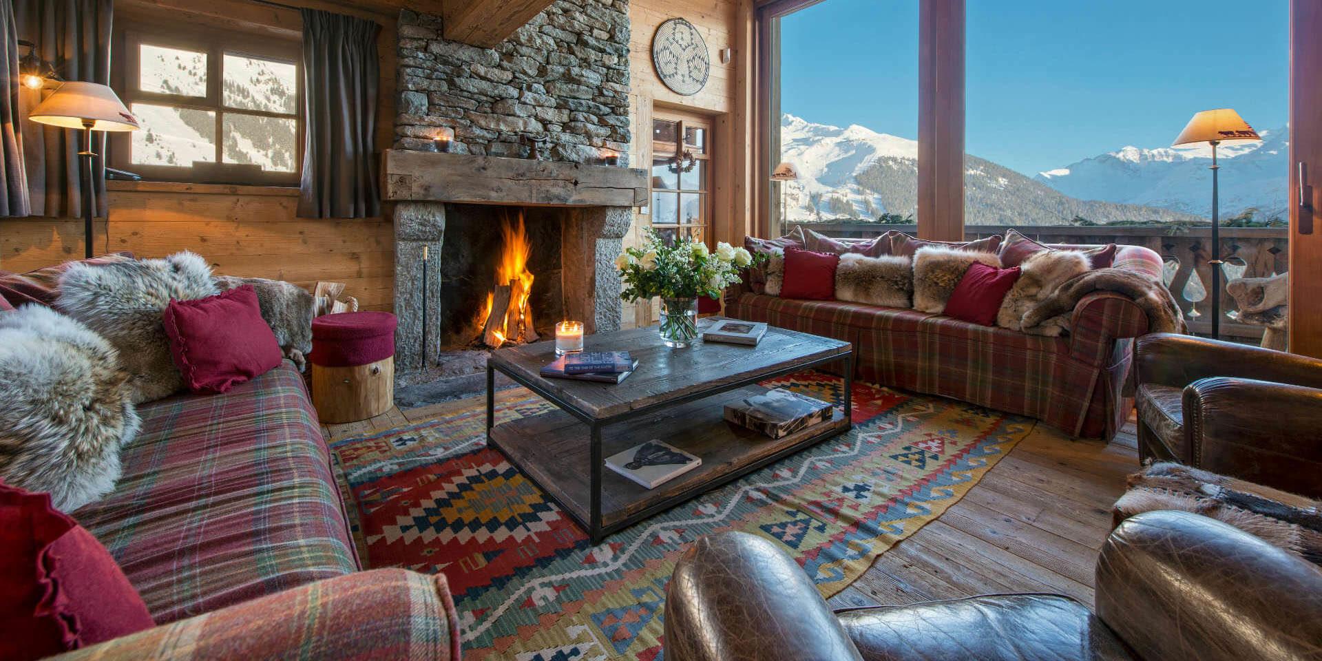 Chalet Nyumba Verbier Les 4 Vallees Zwitserland wintersport skivakantie luxe living open haard banken kussens fauteuil hocker salontafel groot raam uitzicht bergen sneeuw
