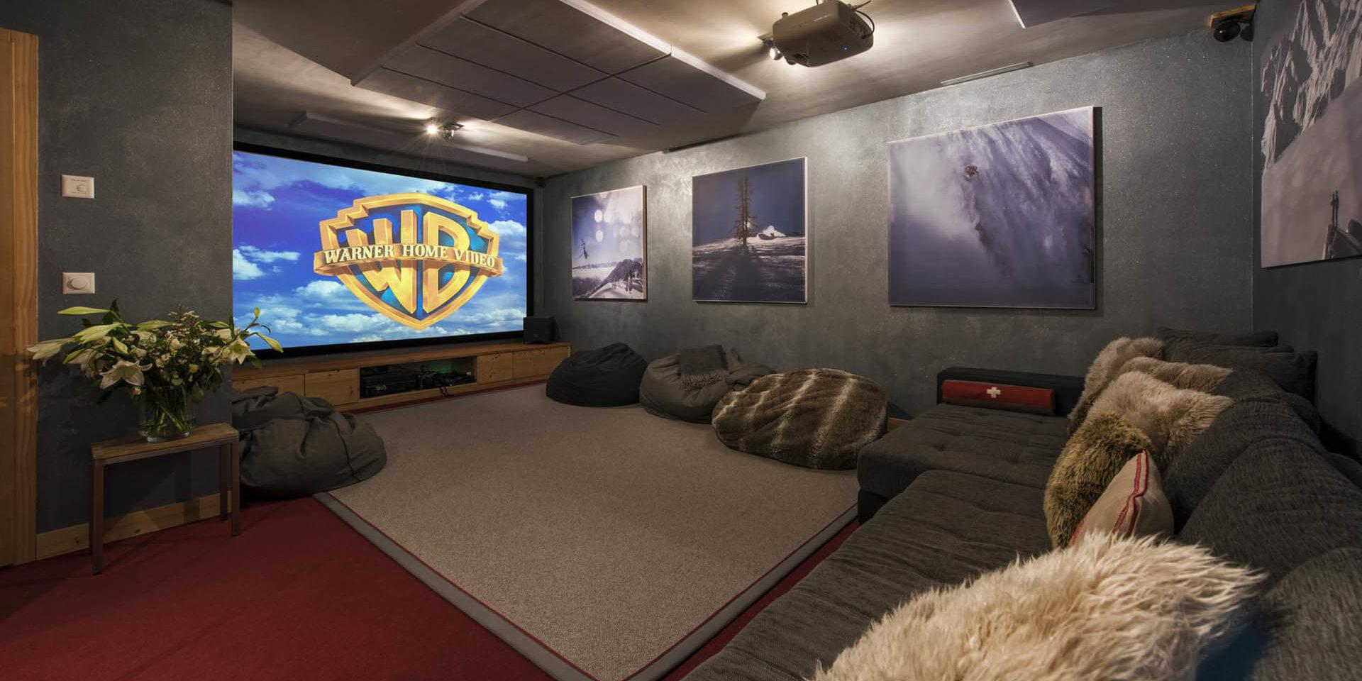 Chalet Rock Verbier Les 4 Vallees Zwitserland wintersport skivakantie luxe bioscoop grote grijze lounge bank zitzakken kussens groot projectiescherm schilderijen