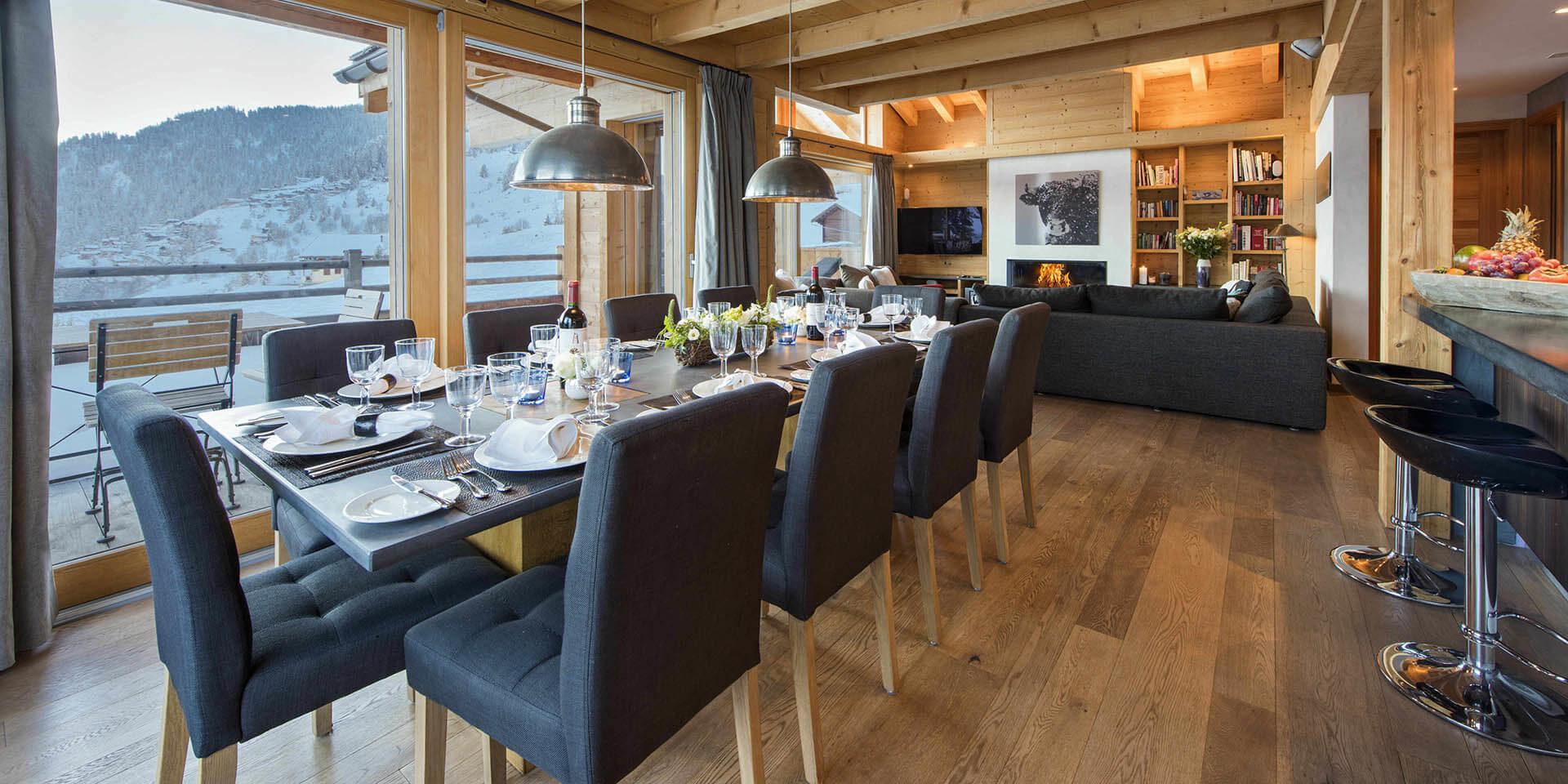 Chalet Rock Verbier Les 4 Vallees Zwitserland wintersport skivakantie luxe eetkamer gedekte tafel wijn wijnglazen lampen barkrukken fruit bank open haard grote ramen balkon uitzicht sneeuw bergen