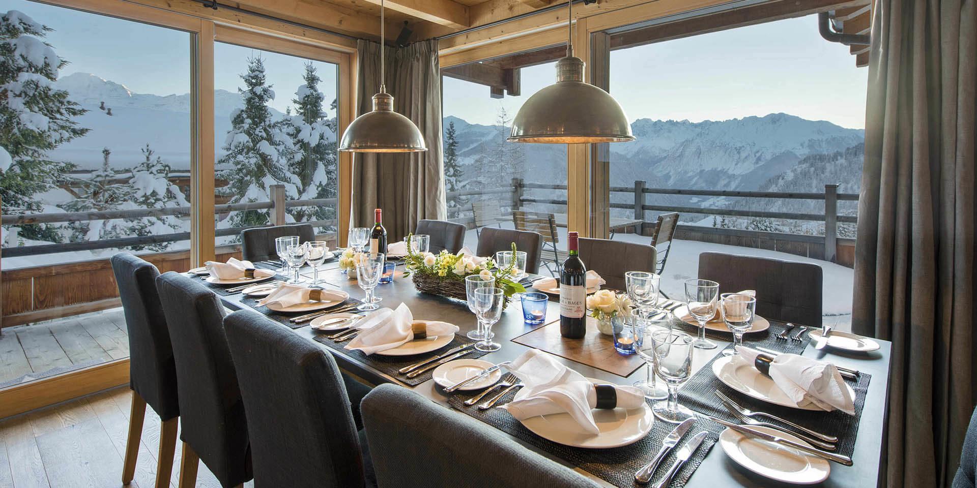 Chalet Rock Verbier Les 4 Vallees Zwitserland wintersport skivakantie luxe eetkamer gedekte tafel wijn wijnglazen lampen balkon stoelen uitzicht besneeuwde bomen bergen sneeuw