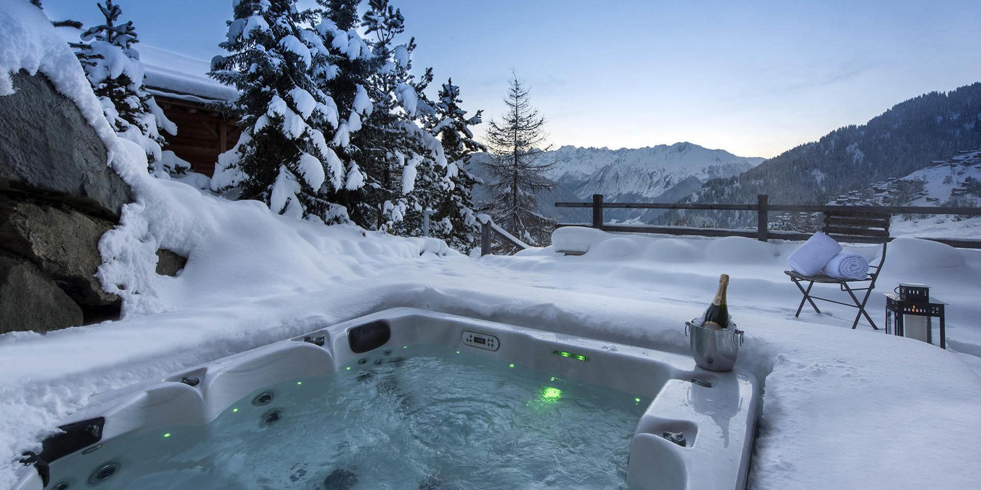Chalet Rock Verbier Les 4 Vallees Zwitserland wintersport skivakantie luxe hot tub Champagne stoel handdoeken ontspannen genieten uitzicht besneeuwde bomen bergen sneeuw