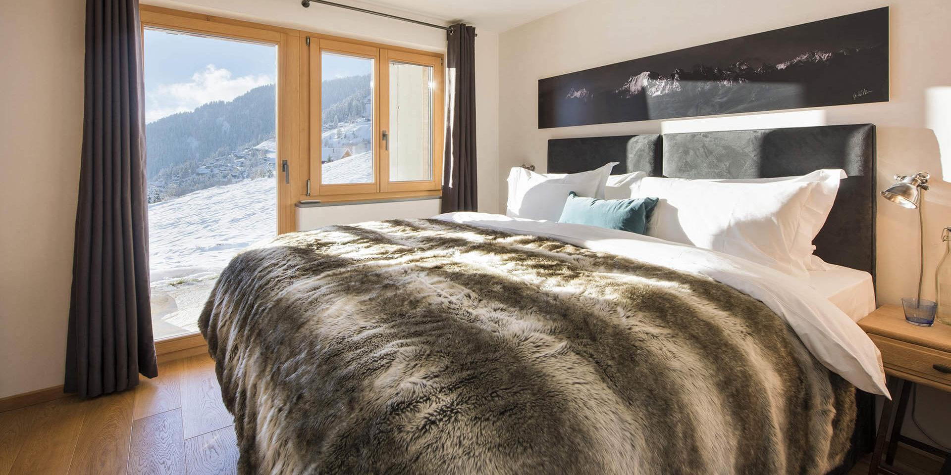 Chalet Rock Verbier Les 4 Vallees Zwitserland wintersport skivakantie luxe slaapkamer 2-persoonsbed bedsprei raam uitzicht sneeuw bomen bergen