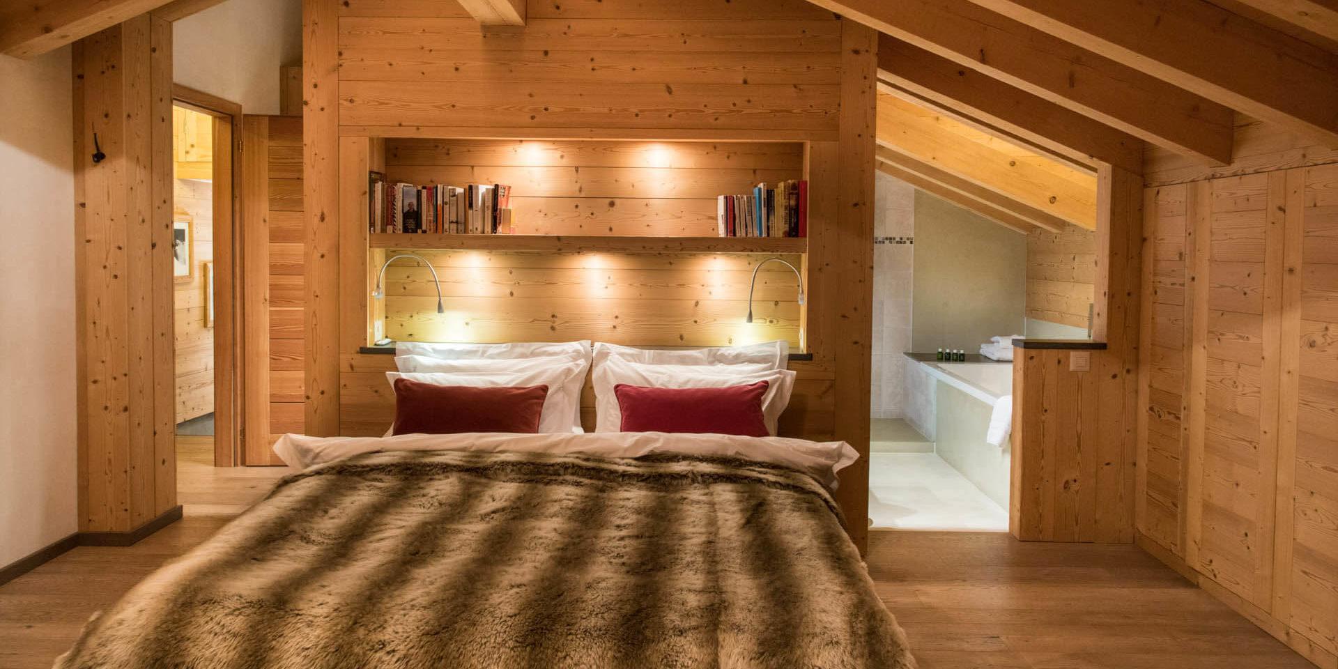 Chalet Rock Verbier Les 4 Vallees Zwitserland wintersport skivakantie luxe slaapkamer 2-persoonsbed bedsprei boeken nachtlampje badkamer bad