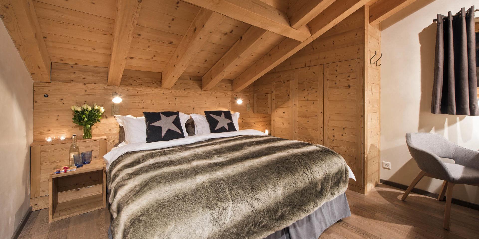 Chalet Rock Verbier Les 4 Vallees Zwitserland wintersport skivakantie luxe slaapkamer 2-persoonsbed bedsprei bloemen nachtlampje stoel