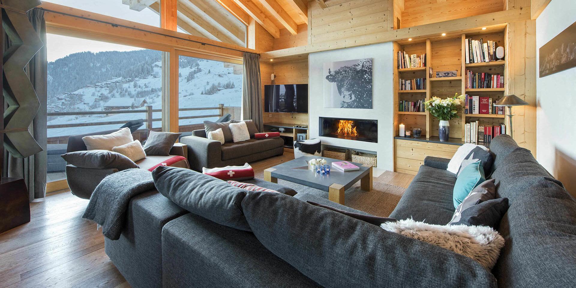 Chalet Rock Verbier Les 4 Vallees Zwitserland wintersport skivakantie luxe hoekbank kussens open haard schilderij koe TV fauteuils boeken hout uitzicht sneeuw besneeuwde bomen bergen