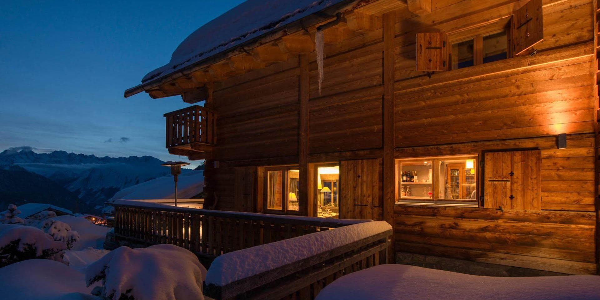Chalet Pierre Avoi Verbier Les 4 Vallees Zwitserland wintersport skivakantie luxe chalet zijkant balkon ligging sneeuw uitzicht bergen by night