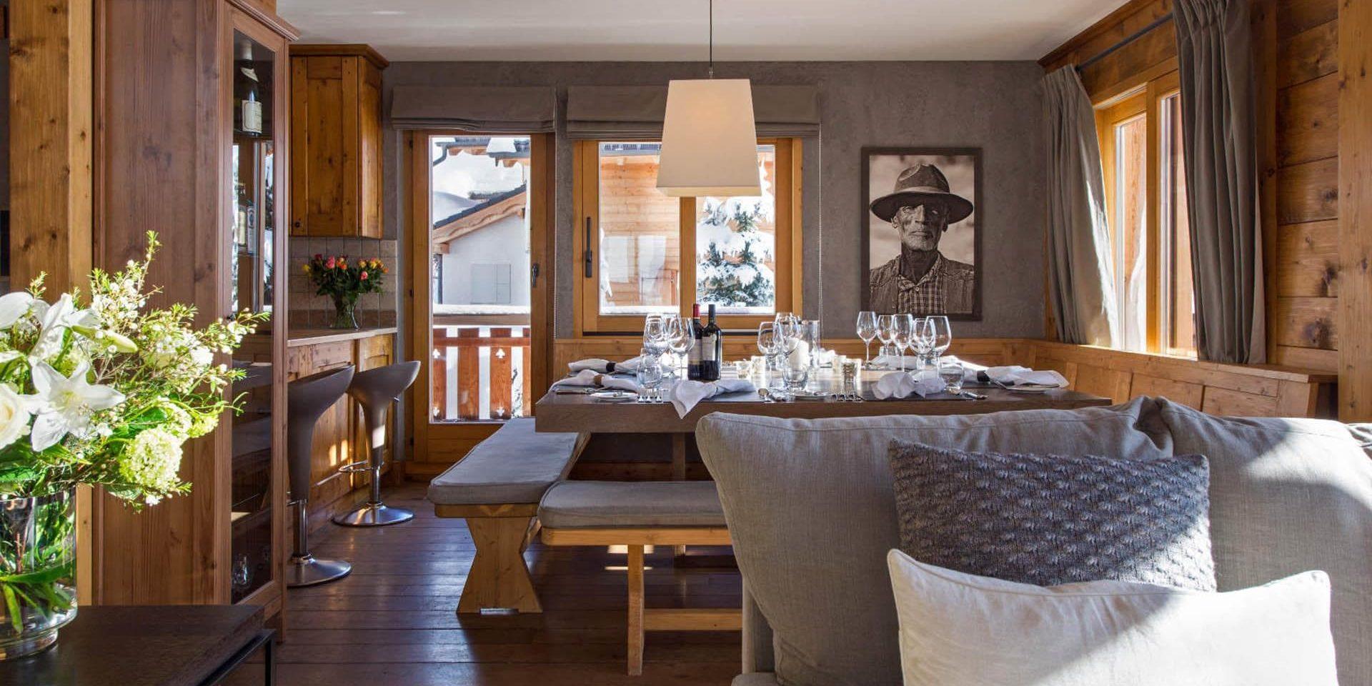 Chalet Pierre Avoi Verbier Les 4 Vallees Zwitserland wintersport skivakantie luxe eetkamer gedekte tafel wijn wijnglazen schilderij bloemen bank barkrukken lamp balkon kussens