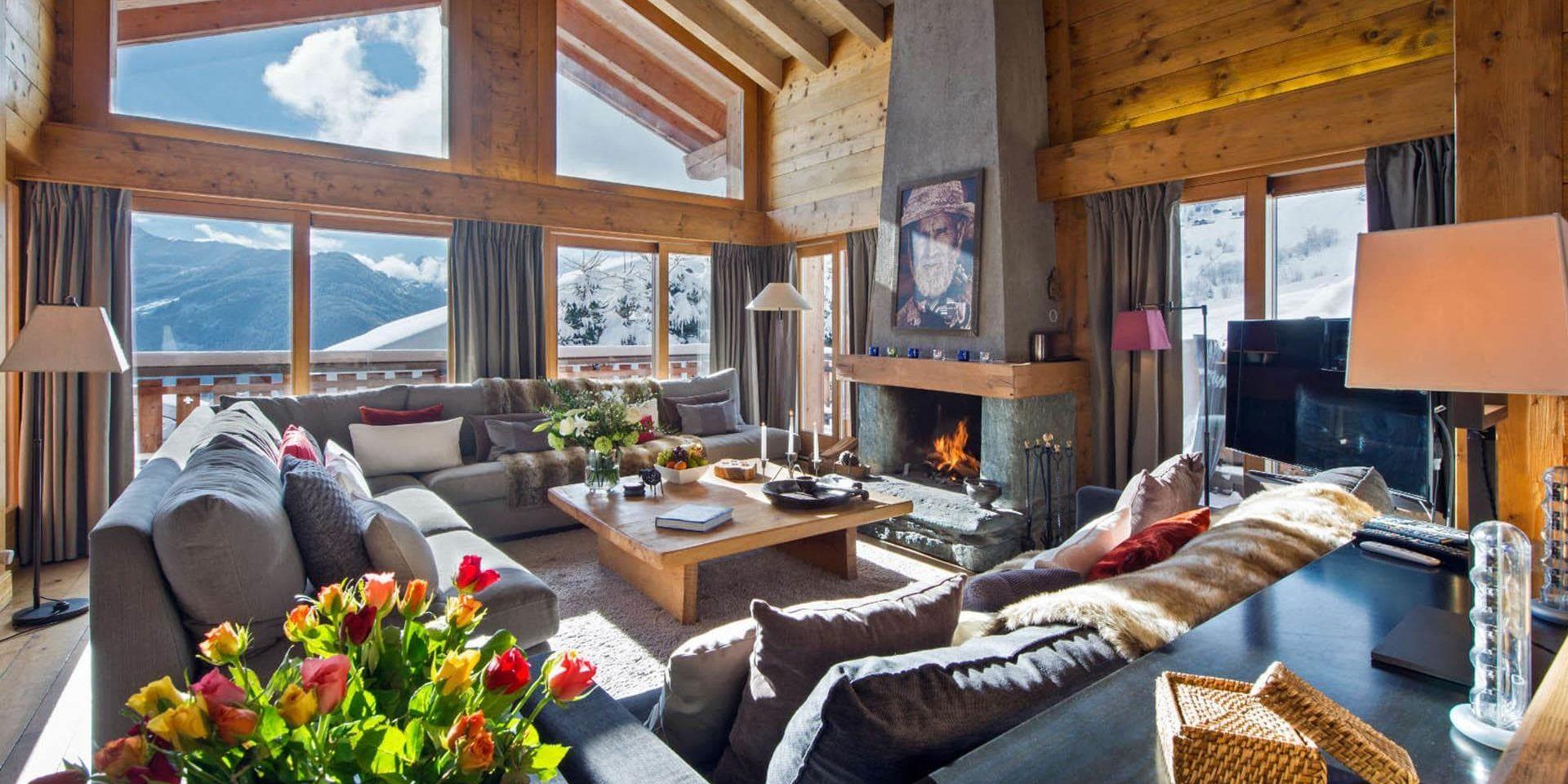 Chalet Pierre Avoi Verbier Les 4 Vallees Zwitserland wintersport skivakantie luxe living open haard schilderij banken kussens bloemen houten balken sneeuw bergen uitzicht