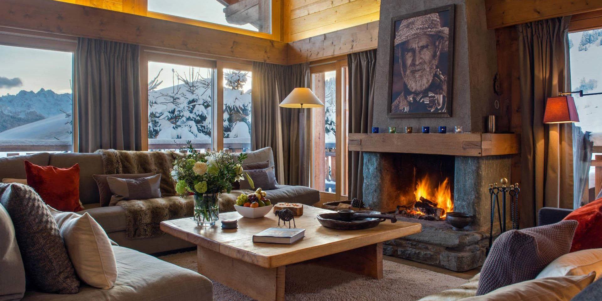 Chalet Pierre Avoi Verbier Les 4 Vallees Zwitserland wintersport skivakantie luxe living open haard schilderij banken kussens bloemen fruit sneeuw bergen uitzicht
