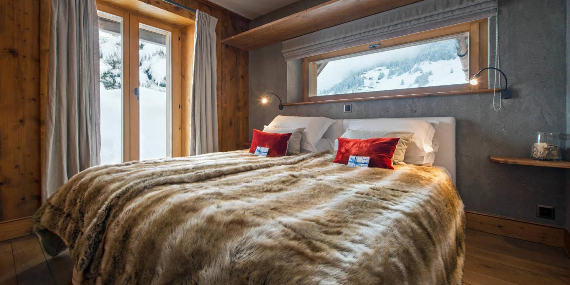 Chalet Pierre Avoi Verbier Les 4 Vallees Zwitserland wintersport skivakantie luxe slaapkamer 2-persoonsbed bedsprei rode kussens raam deur hout uitzicht sneeuw bomen