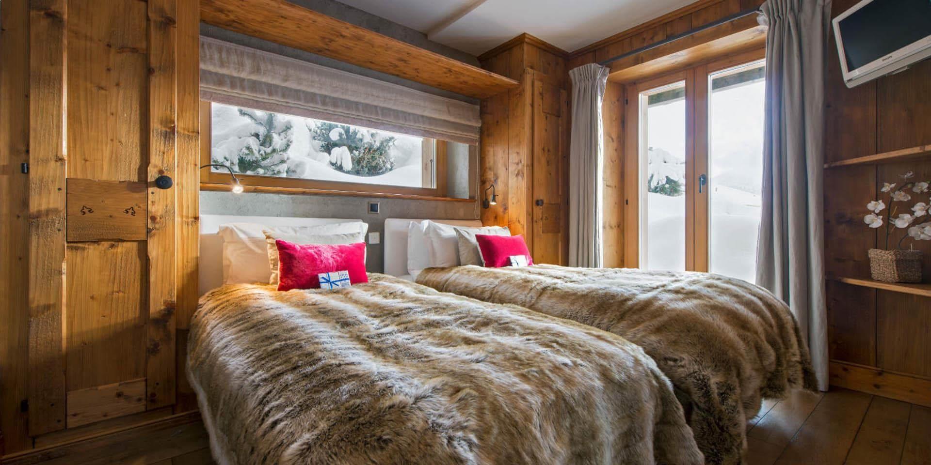 Chalet Pierre Avoi Verbier Les 4 Vallees Zwitserland wintersport skivakantie luxe slaapkamer aparte bedden bedsprei roze kussens raam deur hout TV uitzicht sneeuw bomen