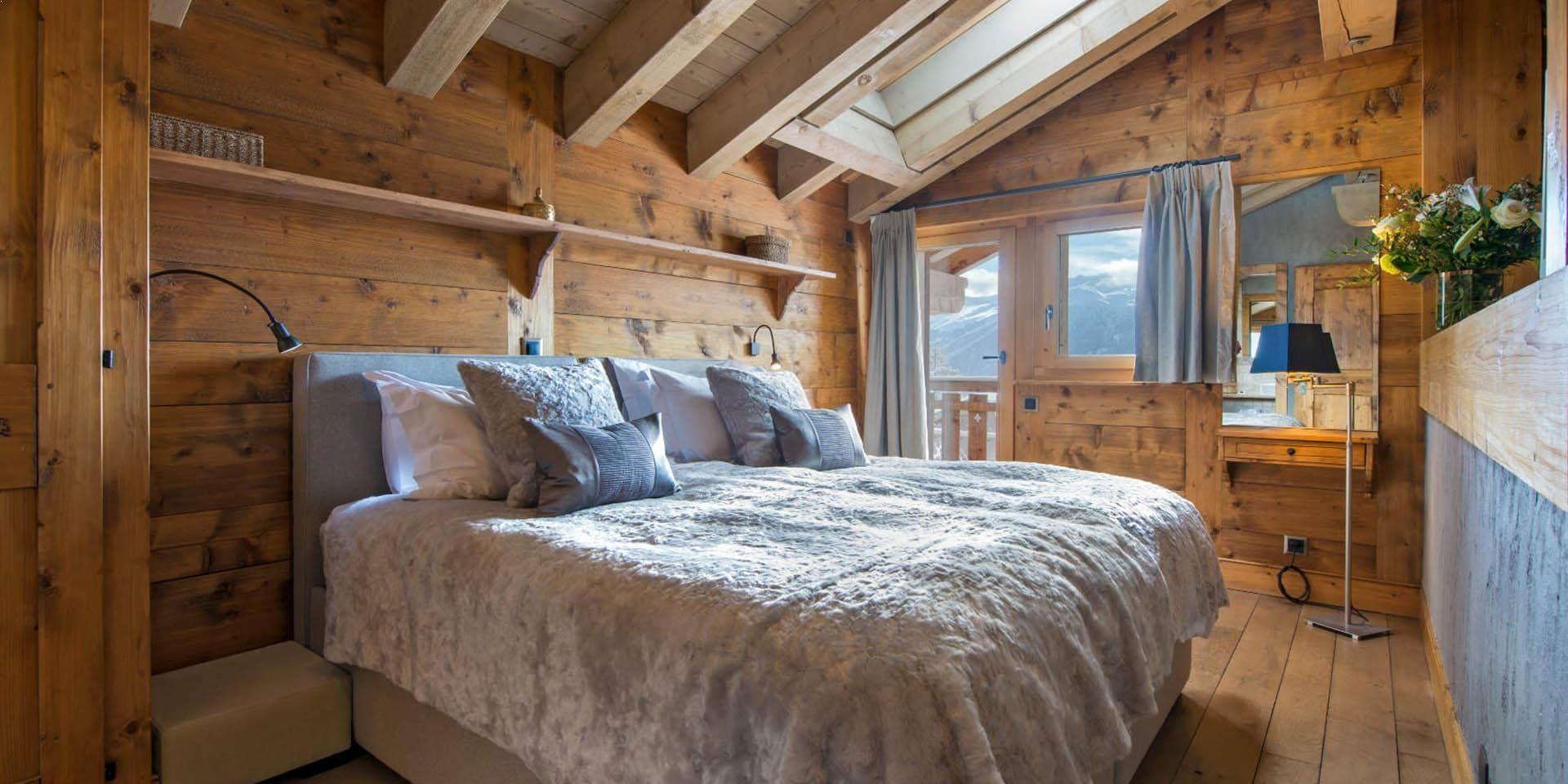 Chalet Pierre Avoi Verbier Les 4 Vallees Zwitserland wintersport skivakantie luxe slaapkamer 2-persoonsbed kussens sprei bloemen balkon sneeuw bomen uitzicht