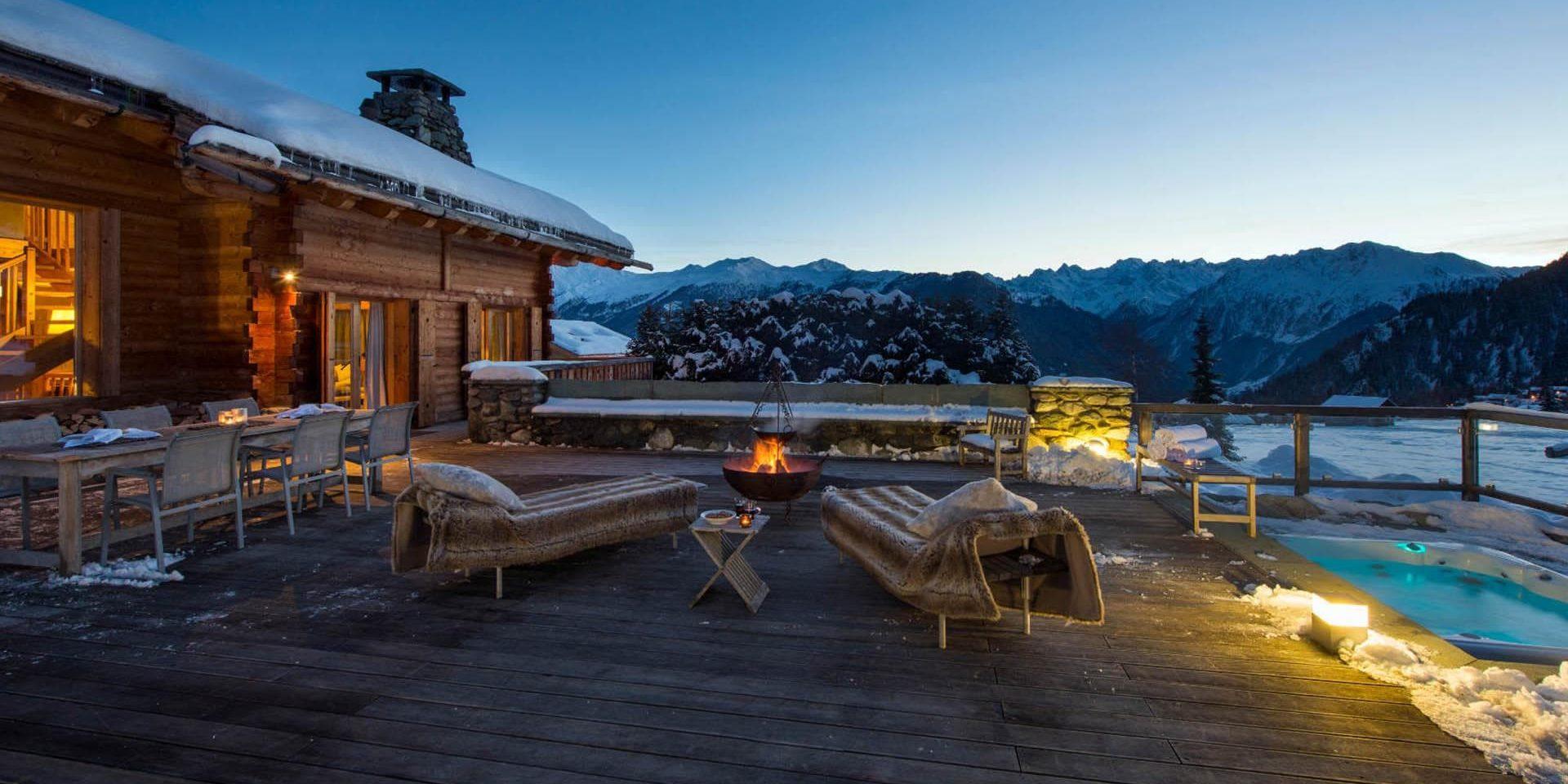 Chalet Pierre Avoi Verbier Les 4 Vallees Zwitserland wintersport skivakantie luxe groot terras hot tub ligstoelen eettafel stoelen vuurkorf sneeuw besneeuwde bomen uitzicht bergen