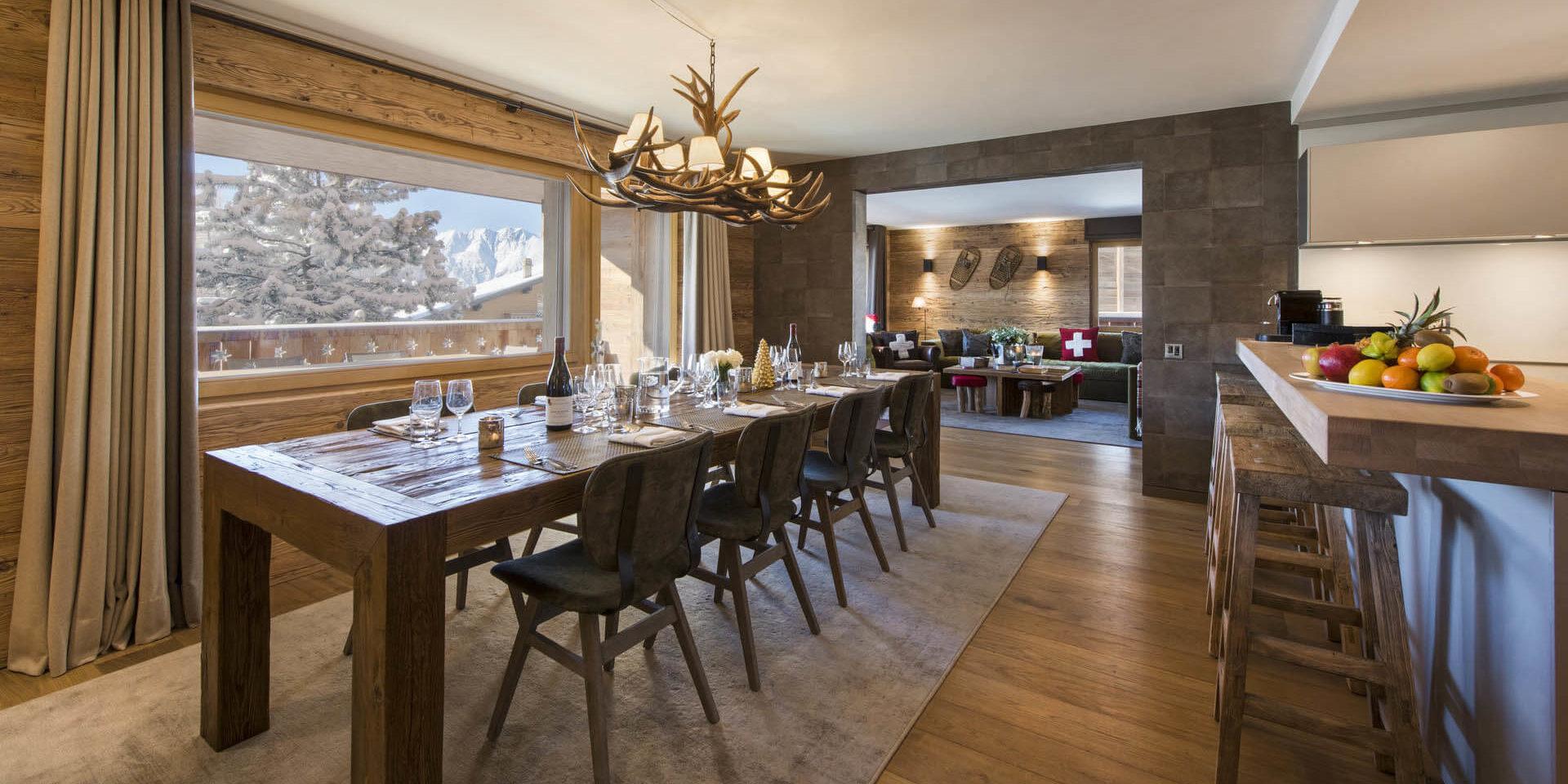 Appartement Rosalp 4 Verbier Les 4 Vallees Zwitserland wintersport skivakantie luxe eetkamer gedekte tafel kroonluchter hout bar barkrukken vers fruit living bank kussens