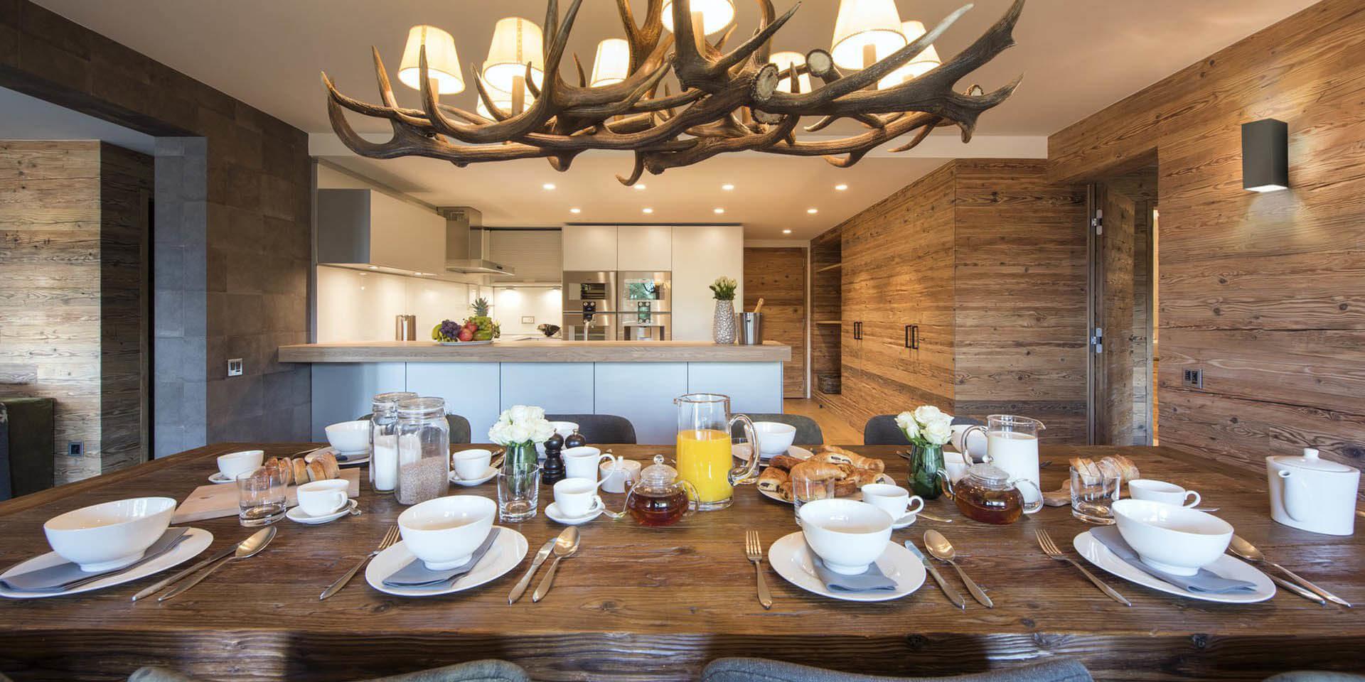 Appartement Rosalp 4 Verbier Les 4 Vallees Zwitserland wintersport skivakantie luxe eetkamer gedekte tafel ontbijt kroonluchter hout keuken bar vers fruit