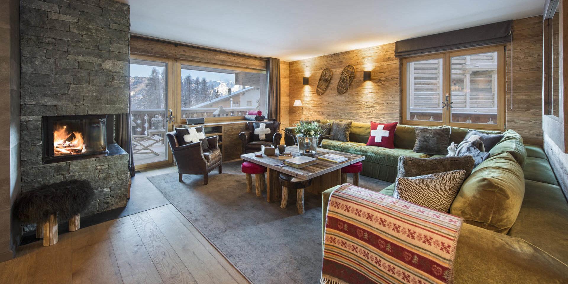 Appartement Rosalp 4 Verbier Les 4 Vallees Zwitserland wintersport skivakantie luxe living open haard groen hoekbank fauteuils kussens kleed balkon uitzicht bomen sneeuw bergen