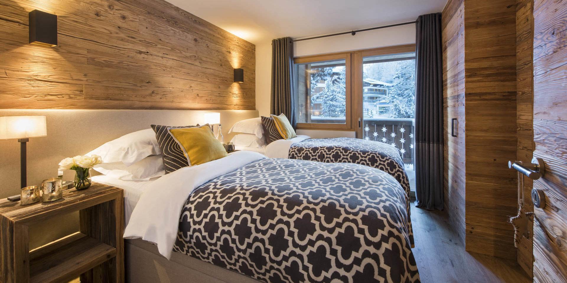 Appartement Rosalp 4 Verbier Les 4 Vallees Zwitserland wintersport skivakantie luxe slaapkamer aparte bedden sprei gele kussens hout balkon besneeuwde bomen