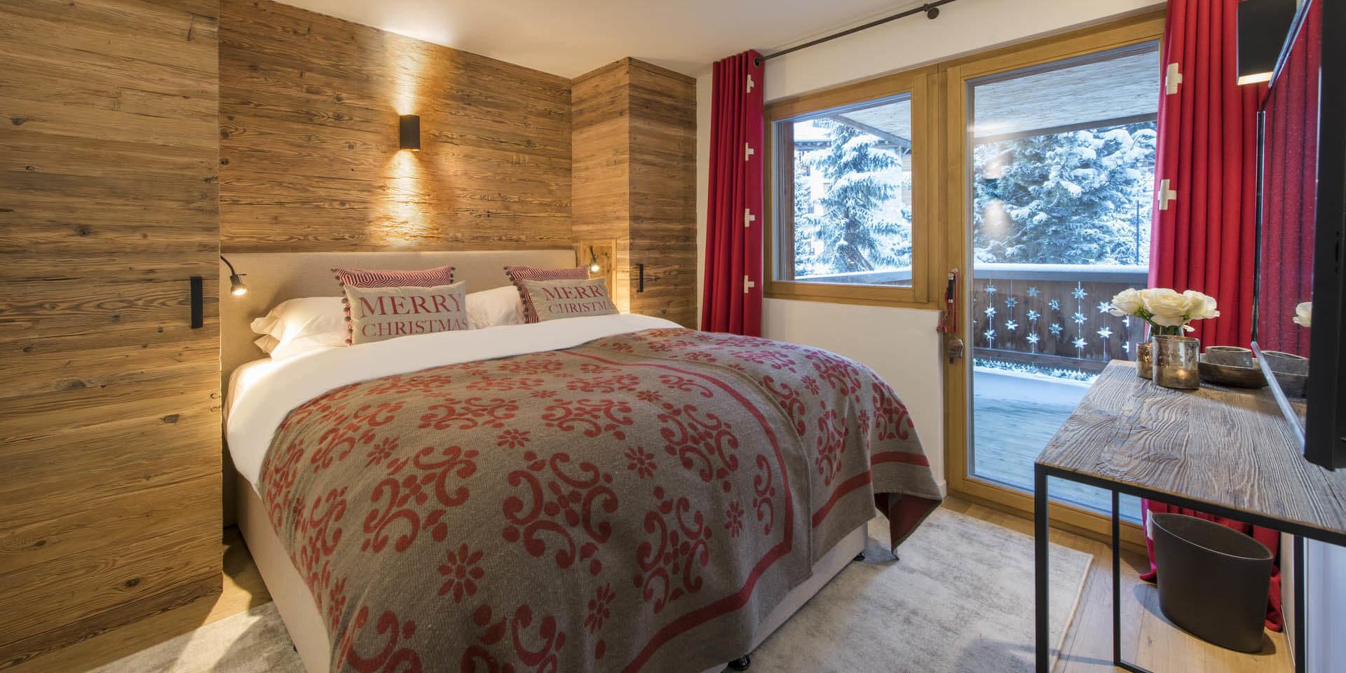 Appartement Rosalp 4 Verbier Les 4 Vallees Zwitserland wintersport skivakantie luxe slaapkamer 2-persoonsbed sprei kussens Merry Christmas tafel rode gordijnen balkon besneeuwde bomen