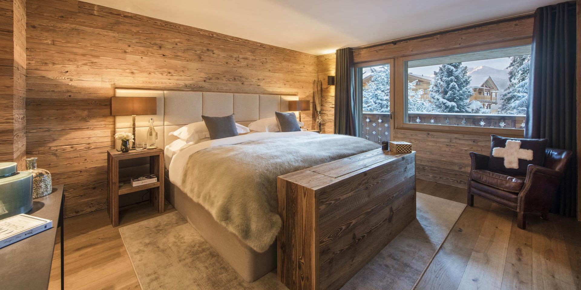 Appartement Rosalp 4 Verbier Les 4 Vallees Zwitserland wintersport skivakantie luxe slaapkamer 2-persoonsbed tafel fauteuil sprei nachtlampjes balkon besneeuwde bomen