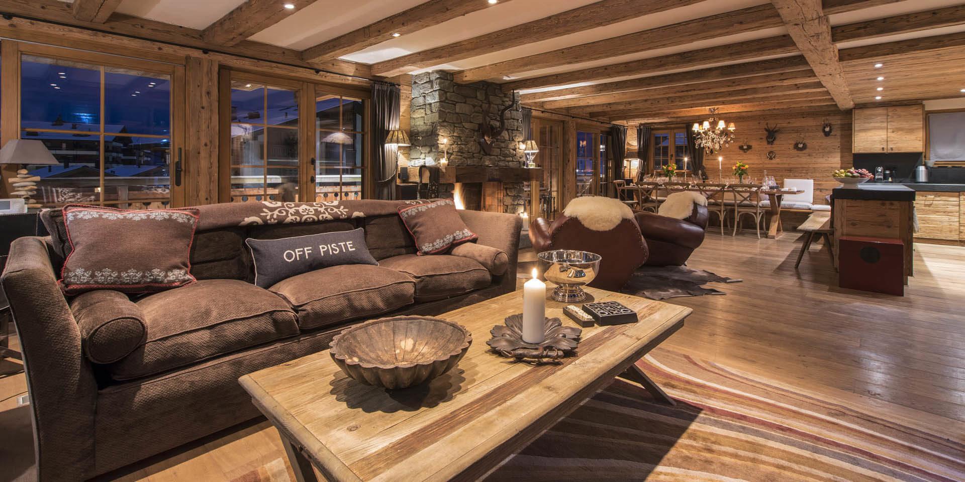 Appartement Silver Verbier Les 4 Vallees Zwitserland wintersport skivakantie luxe living bruine bank kussens Off piste kaarsen salontafel fauteuils open haard eetkamer keuken houten balken balkon sneeuw