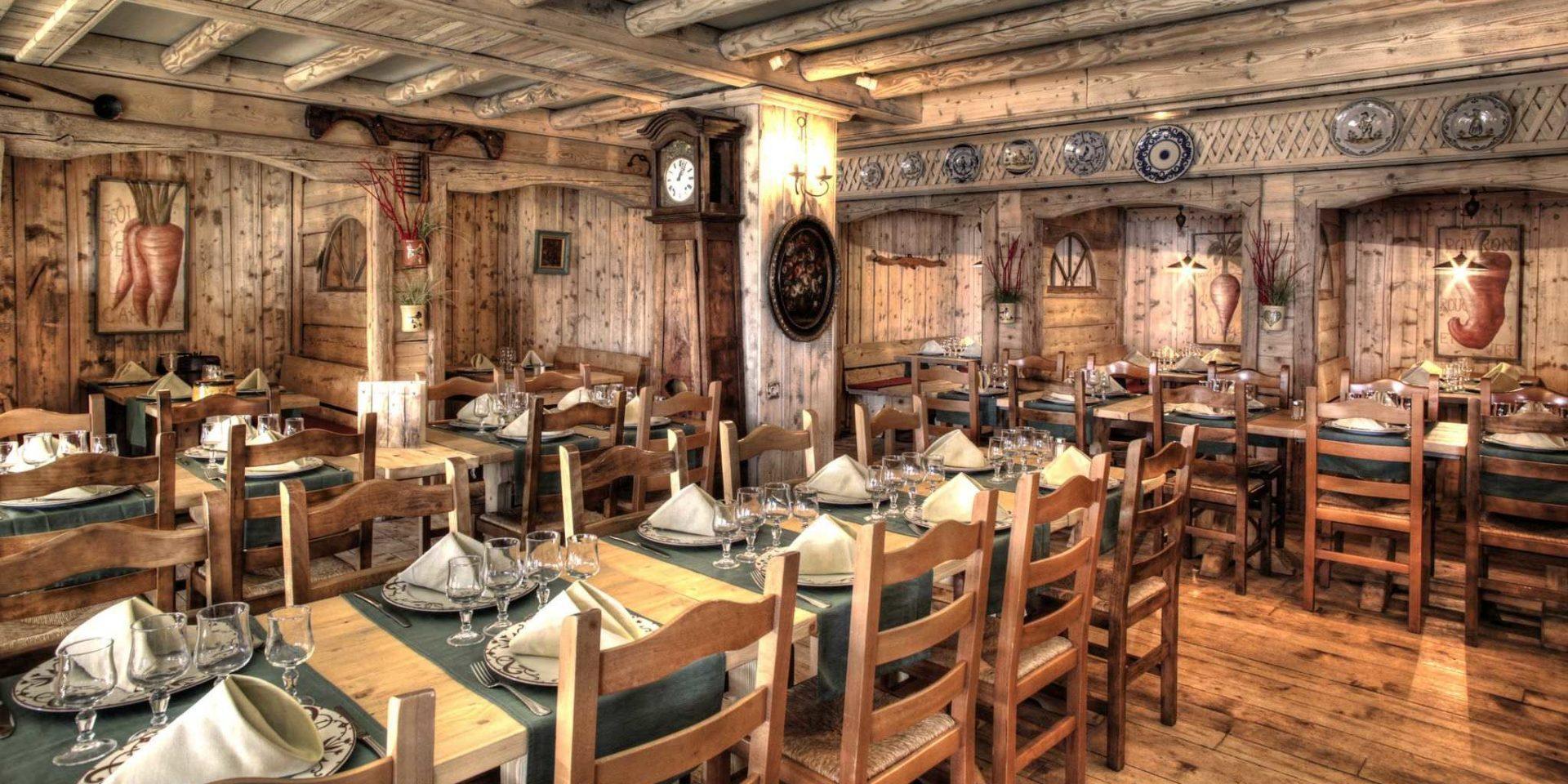Hotel Village Montana Tignes Tignes-Val d'Isere Frankrijk wintersport skivakantie luxe restaurant La Chaumiere gedekte tafels wijnglazen schilderijen klok veel hout houten wanden houten plafond houten balken