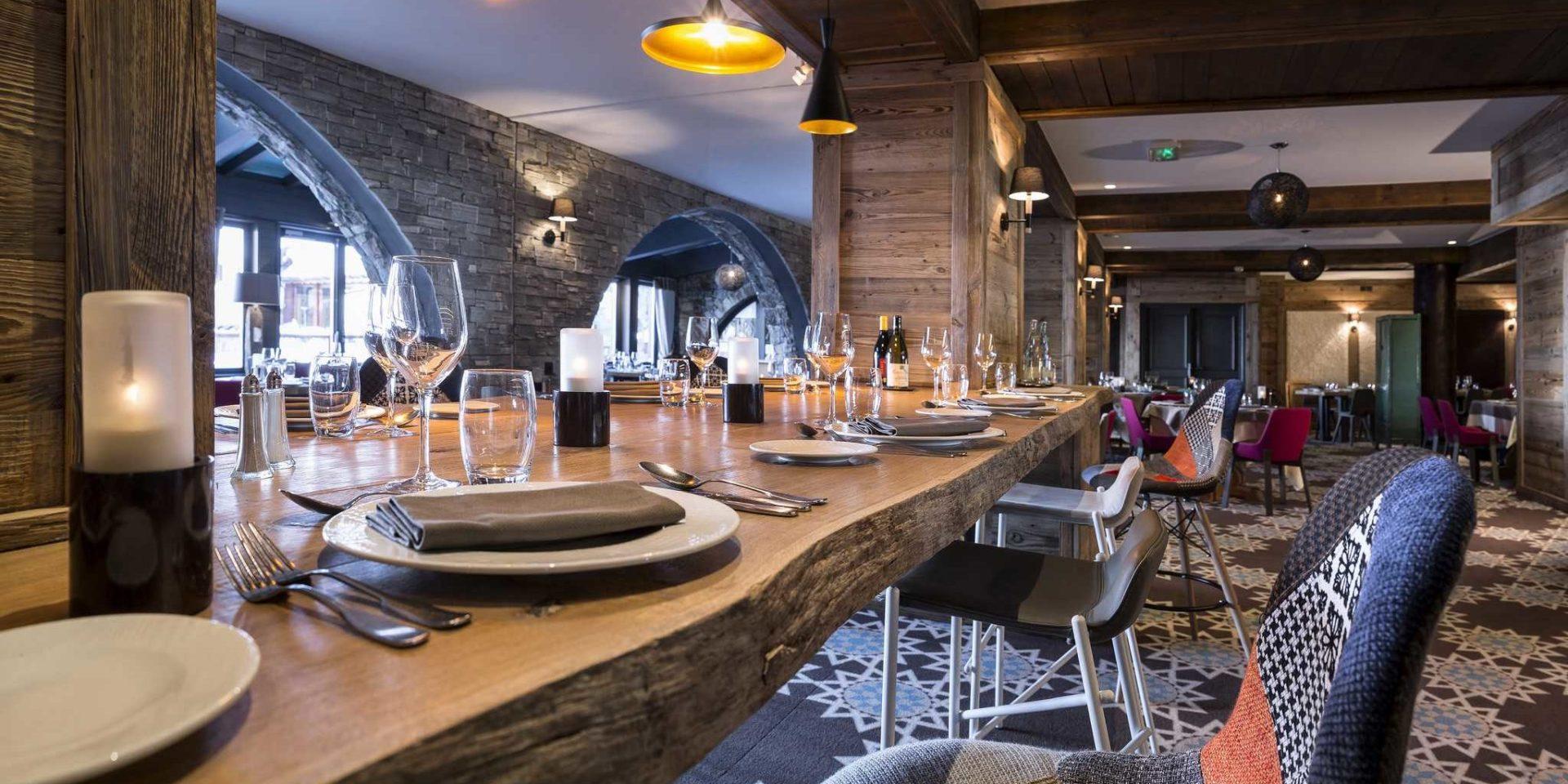 Hotel Village Montana Tignes Tignes-Val d'Isere Frankrijk wintersport skivakantie luxe restaurant Les Chanterelles gedekte tafels boomstam gekleurde stoelen kaarsen glazen patroon vloerbedekking houten wanden half ronde ramen bogen hanglampen