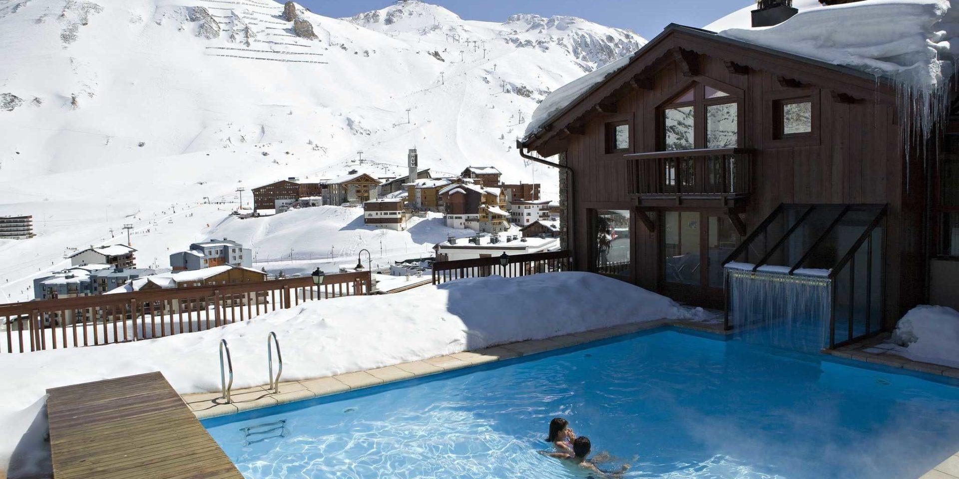 Hotel Village Montana Tignes Tignes-Val d'Isere Frankrijk wintersport skivakantie luxe buiten zwembad mensen Hotel Village Montana dorp Tignes besneeuwde bergen sneeuw zwemmen ontspannen relaxen genieten