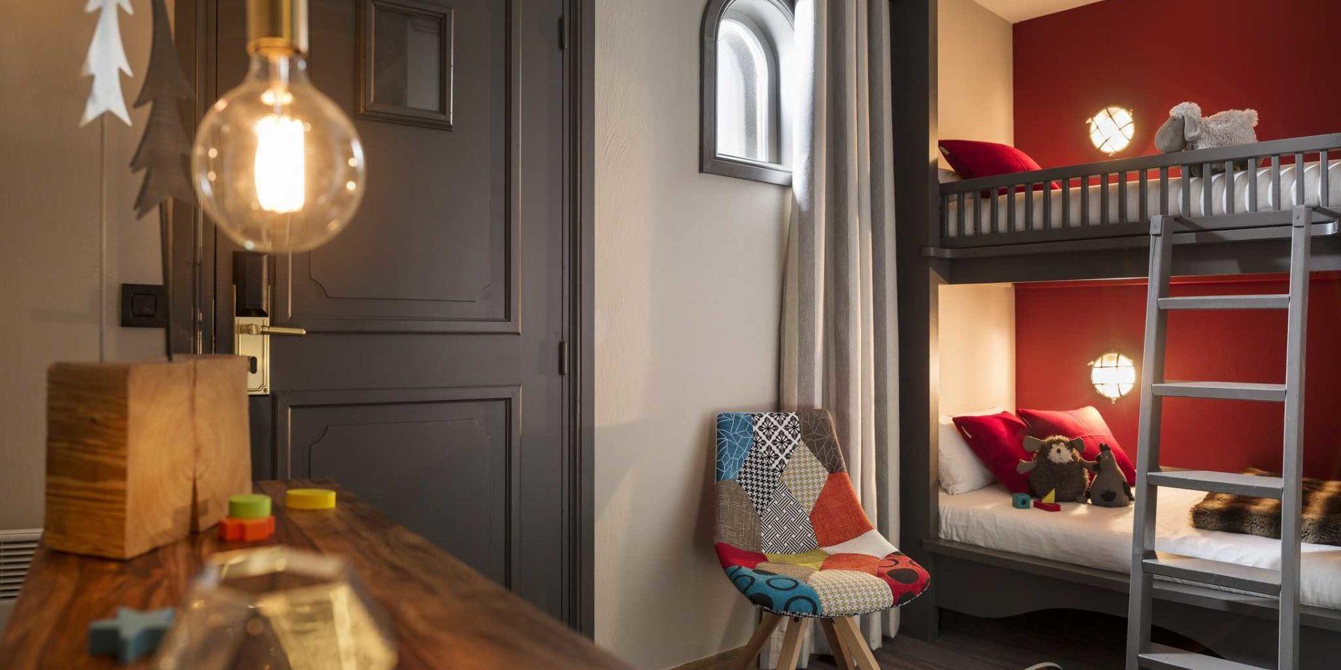 Hotel Village Montana Tignes Tignes-Val d'Isere Frankrijk wintersport skivakantie luxe slaapkamer stapelbed rode muur rode kussens knuffels speelgoed kinderkamer gekleurde stoel lamp trap