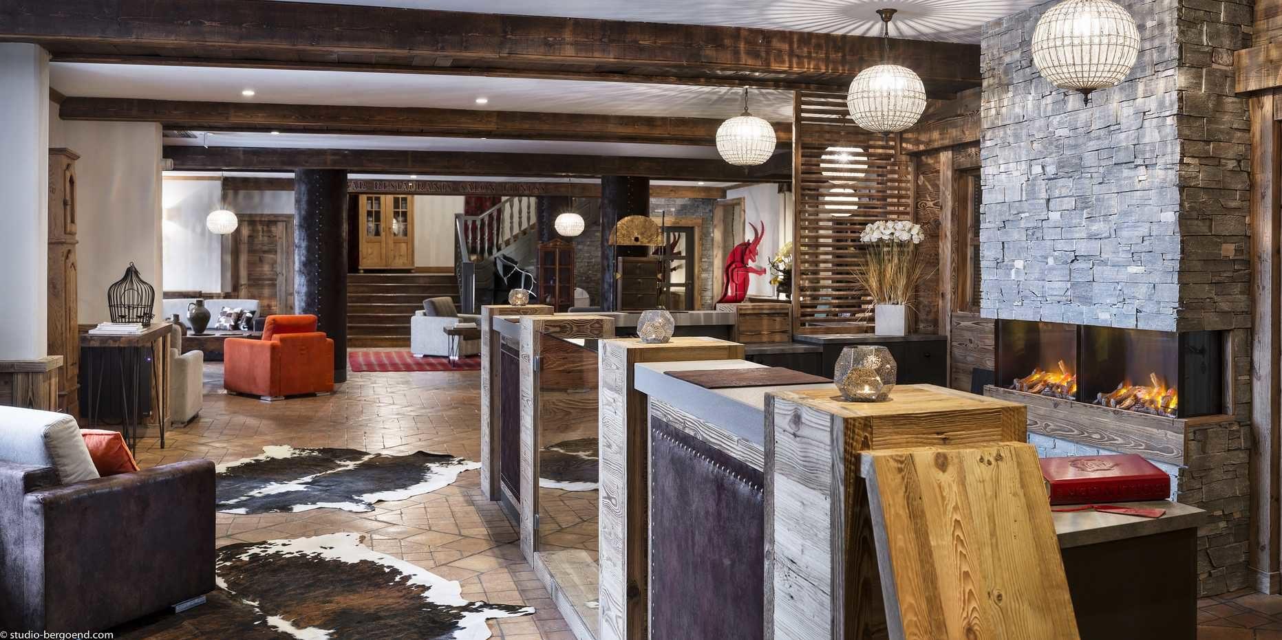 Hotel Village Montana Tignes Tignes-Val d'Isere Frankrijk wintersport skivakantie luxe lounge open haard stenen muur oranje bruine fauteuils vloerkleden hanglampen trap houten balken
