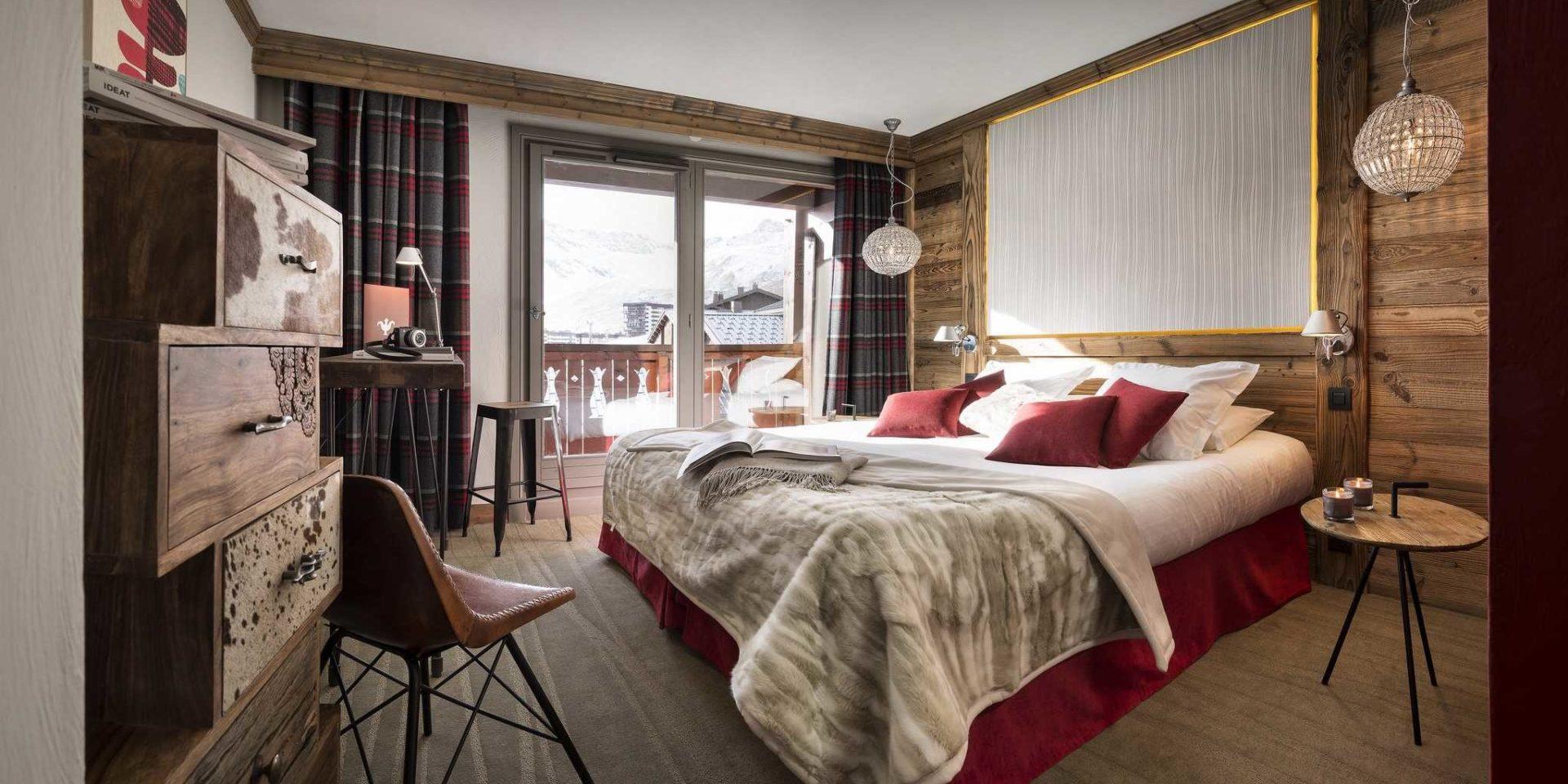 Hotel Village Montana Tignes Tignes-Val d'Isere Frankrijk wintersport skivakantie luxe slaapkamer 2-persoonsbed rode kussens sprei handlamp tafeltje bruine stoel kast geblokte gordijnen balkon bergen