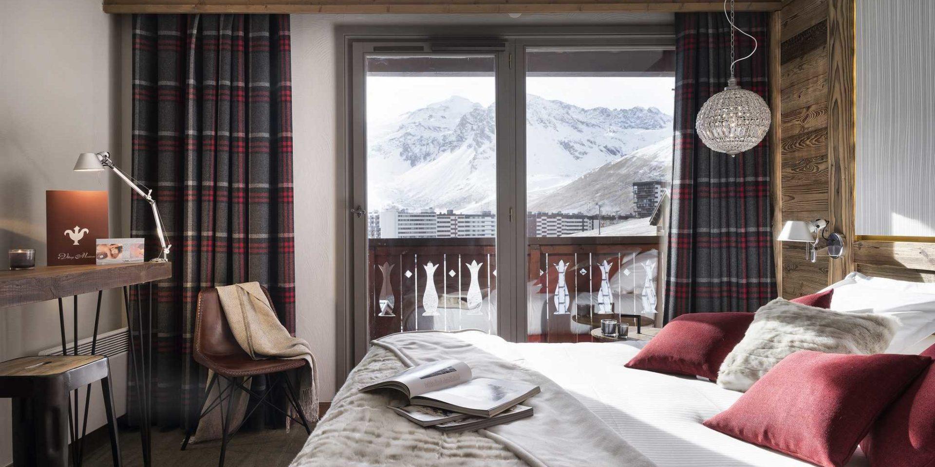 Hotel Village Montana Tignes Tignes-Val d'Isere Frankrijk wintersport skivakantie luxe slaapkamer 2-persoonsbed rode kussens sprei handlamp bruine stoel geblokte gordijnen balkon besneeuwde bergen