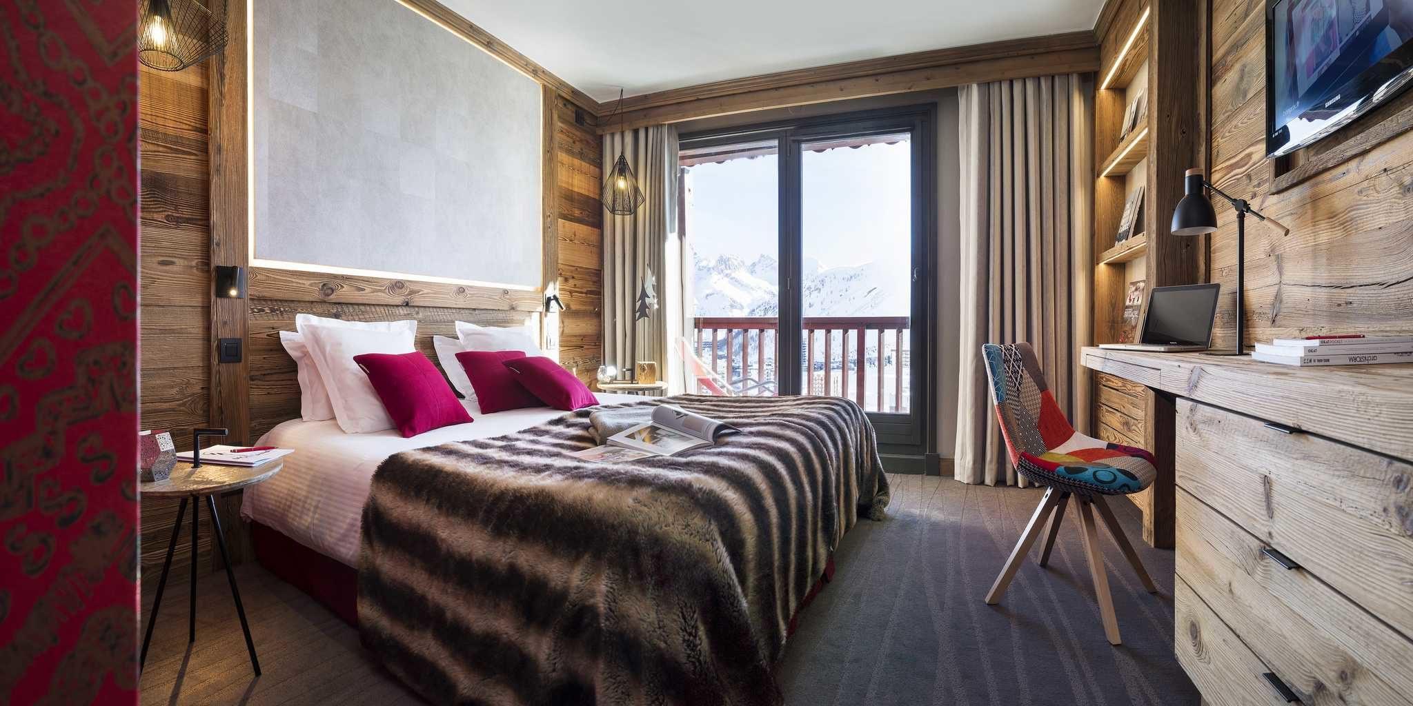 Hotel Village Montana Tignes Tignes-Val d'Isere Frankrijk wintersport skivakantie luxe slaapkamer 2-persoonsbed roze kussens sprei gekleurde stoel bureau TV hanglampen raam balkon besneeuwde bergen