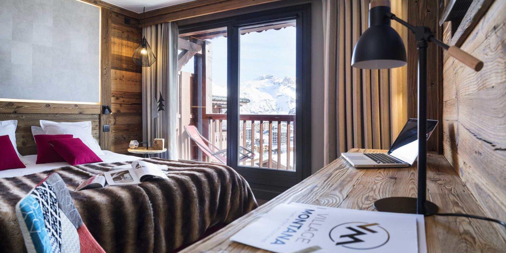 Hotel Village Montana Tignes Tignes-Val d'Isere Frankrijk wintersport skivakantie luxe slaapkamer 2-persoonsbed roze kussens sprei boeken gekleurde stoel bureau bureaulamp raam balkon ligstoel besneeuwde bergen