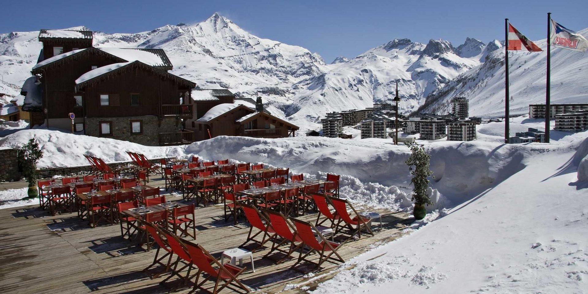 Hotel Village Montana Tignes Tignes-Val d'Isere Frankrijk wintersport skivakantie luxe restaurant La Chaumiere terras rode ligstoelen tafels rode stoelen plant vlaggen dorp Tignes besneeuwde bergen sneeuw