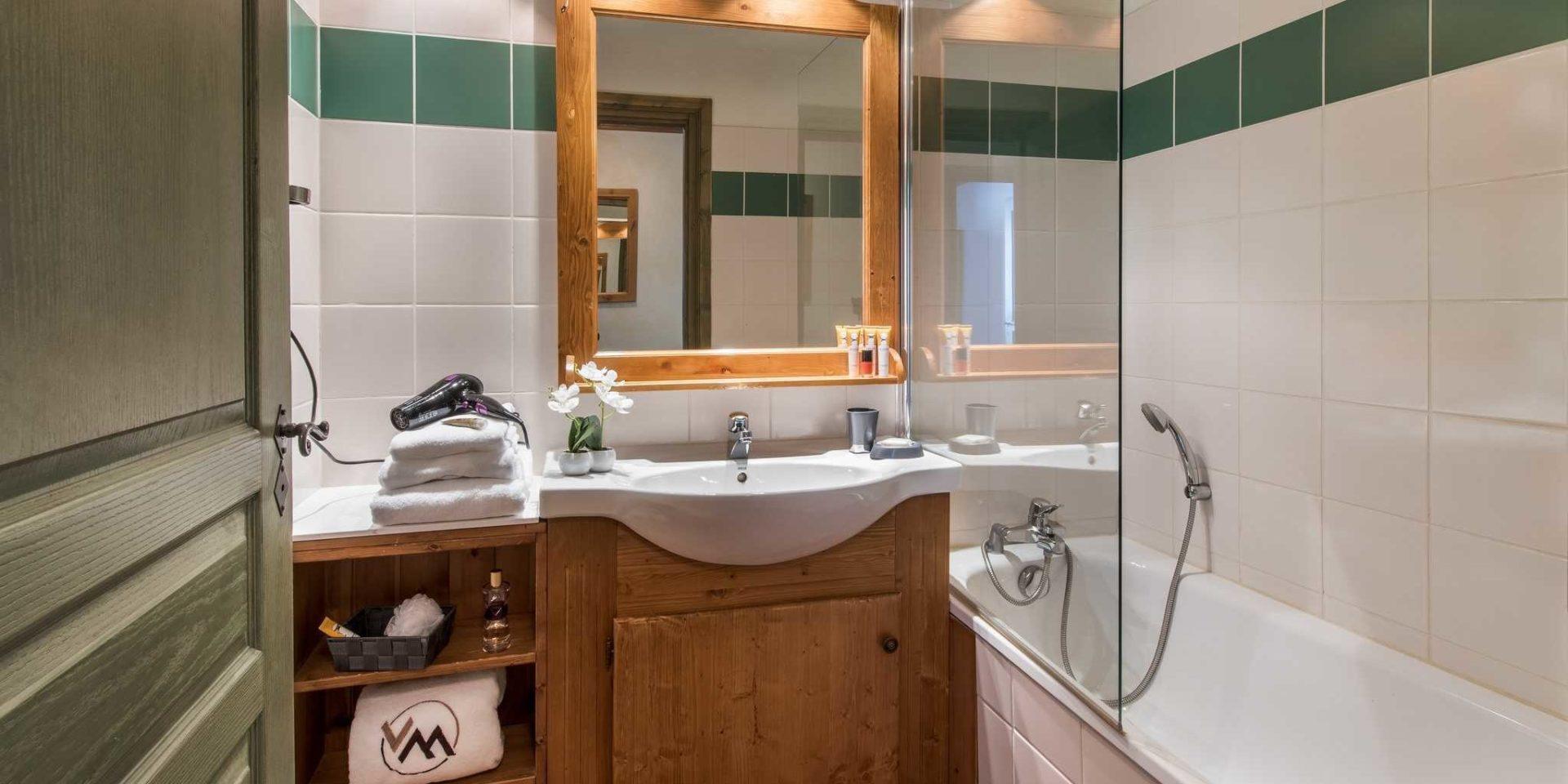 Residences Village Montana Tignes Tignes-Val d'Isere Frankrijk wintersport skivakantie luxe badkamer bad spiegel wastafel fohn handdoeken groene rand tegels