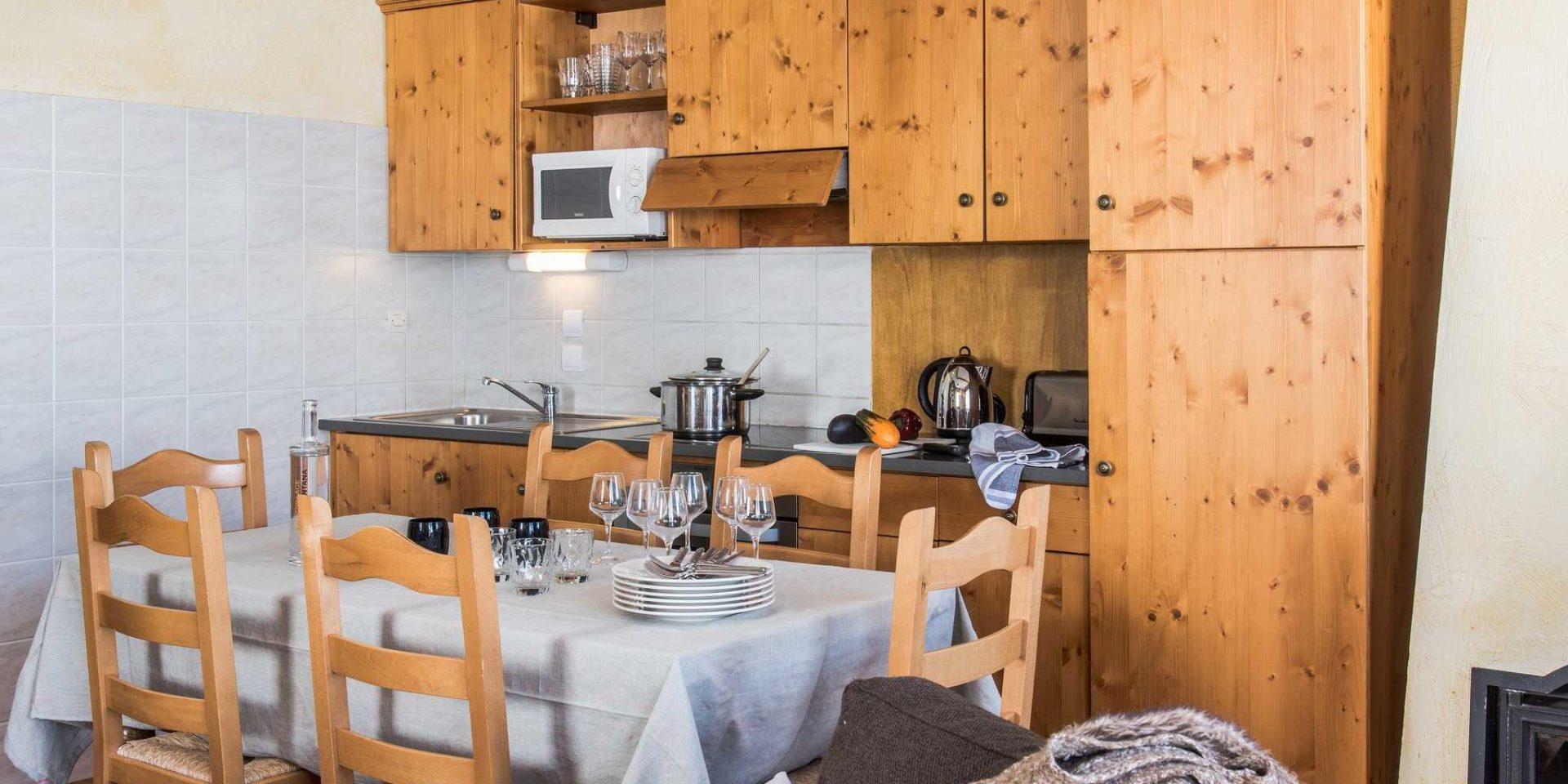 Residences Village Montana Tignes Tignes-Val d'Isere Frankrijk wintersport skivakantie luxe keuken 5K8 eettafel wijnglazen houten stoelen houten kastjes kookplaat pan waterkoker