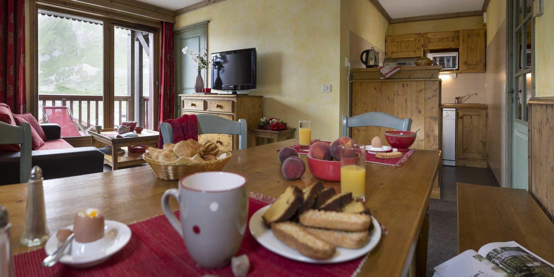 Residences Village Montana Tignes Tignes-Val d'Isere Frankrijk wintersport skivakantie luxe living 3K6 gedekte tafel ontbijt broodjes perziken eieren houten stoelen bankje rode bank salontafel thee TV vaas bloem balkon rode ligstoel keuken