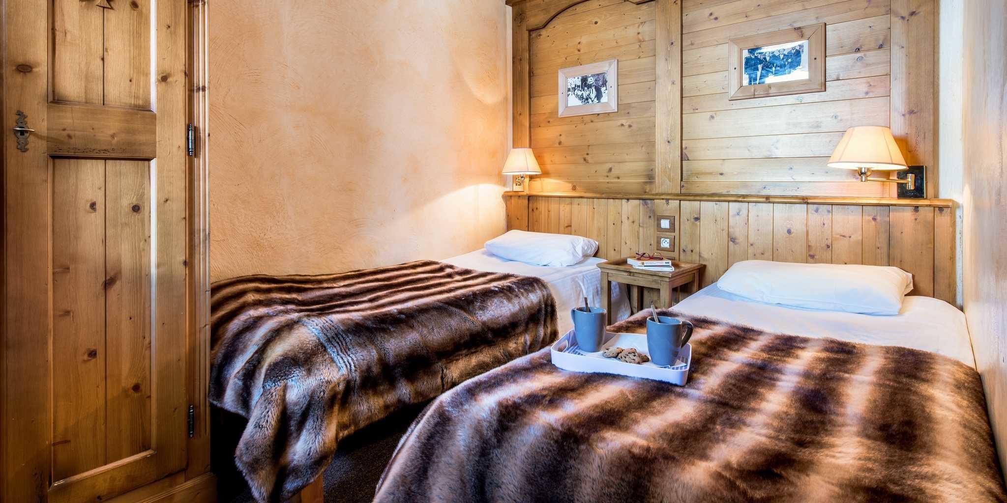 Residences Village Montana Tignes Tignes-Val d'Isere Frankrijk wintersport skivakantie luxe slaapkamer aparte bedden theekopjes koekjes houten wand schilderijen wandlampjes