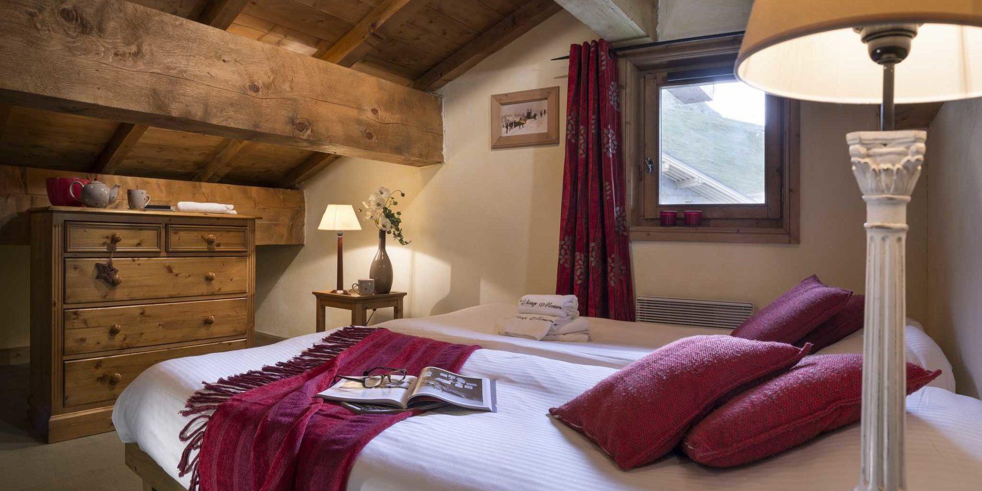 Residences Village Montana Tignes Tignes-Val d'Isere Frankrijk wintersport skivakantie luxe slaapkamer aparte bedden kleed rode kussens kast nachtlampje theepot schilderij raam rood gordijn rode kaarsen houten balken bomen
