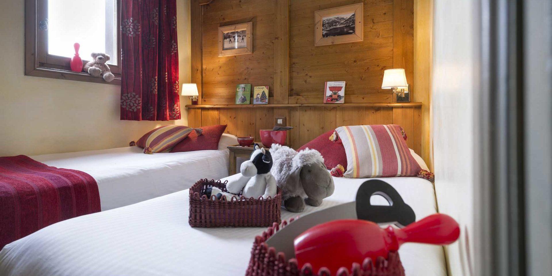 Residences Village Montana Tignes Tignes-Val d'Isere Frankrijk wintersport skivakantie luxe slaapkamer aparte bedden rode gestreepte kussens knuffels speelgoed beer boekjes houten wand schilderijen wandlampjes
