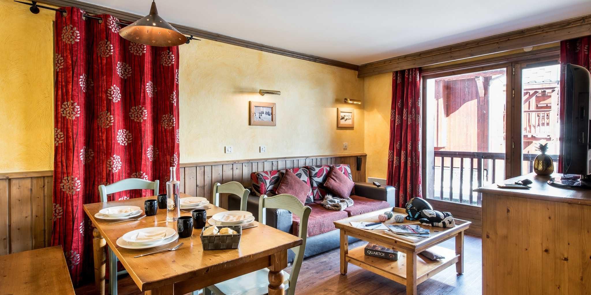 Residences Village Montana Tignes Tignes-Val d'Isere Frankrijk wintersport skivakantie luxe living 3K6 gedekte tafel karaf bank kussens salontafel boek TV rode gordijnen schilderijen balkon
